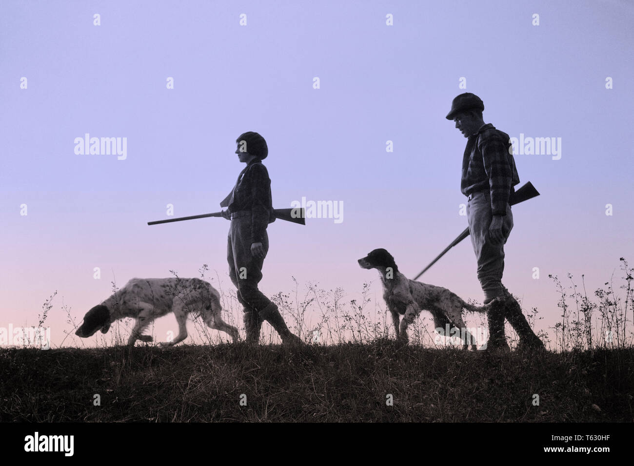 1920s 1930s ANONYMOUS SILHOUETTE MAN AND WOMAN HUNTERS CARRYING GUNS EACH WITH A HUNTING DOG  - s2541b HAR001 HARS LEISURE SILHOUETTED AND CANINES RECREATION POOCH CONNECTION ANONYMOUS CANINE COOPERATION FIREARM FIREARMS HUNTERS MAMMAL MID-ADULT MID-ADULT MAN MID-ADULT WOMAN TOGETHERNESS BLACK AND WHITE HAR001 OLD FASHIONED - Stock Image