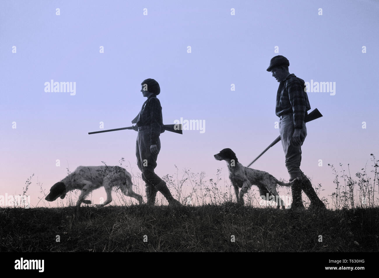 1920s 1930s ANONYMOUS SILHOUETTE MAN AND WOMAN HUNTERS CARRYING GUNS EACH WITH A HUNTING DOG  - s2541c HAR001 HARS LEISURE SILHOUETTED AND CANINES RECREATION POOCH CONNECTION ANONYMOUS CANINE COOPERATION FIREARM FIREARMS HUNTERS MAMMAL MID-ADULT MID-ADULT MAN MID-ADULT WOMAN TOGETHERNESS BLACK AND WHITE HAR001 OLD FASHIONED - Stock Image