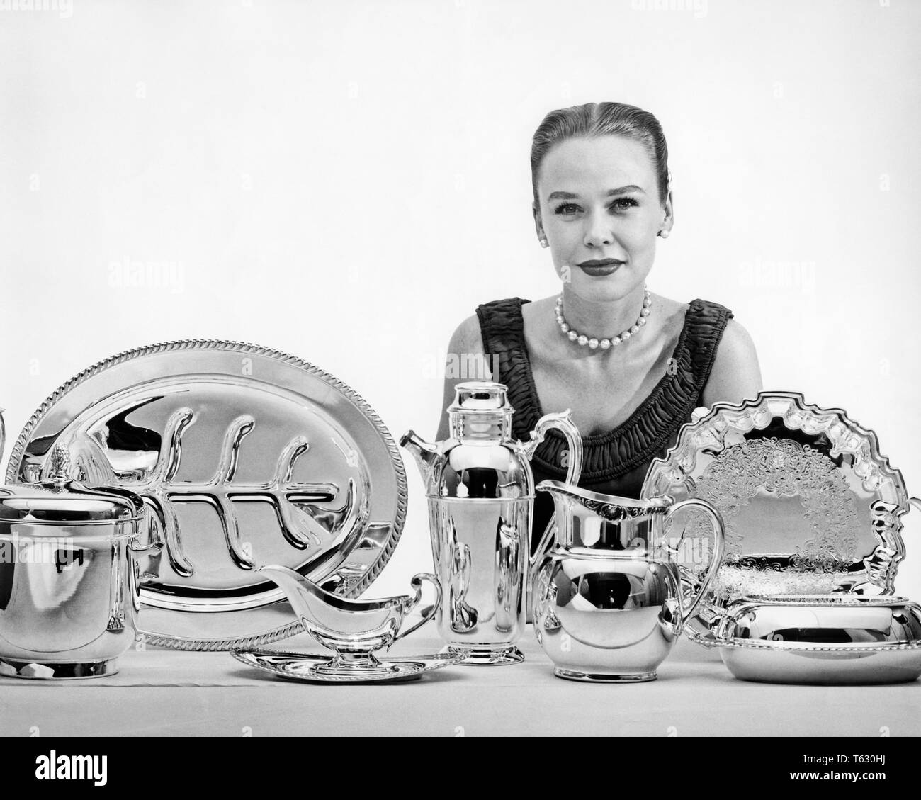 1950s ELEGANT WOMAN LOOKING AT CAMERA POSING BEHIND ARRAY OF STERLING AND SILVER PLATE SERVING PIECES - s3057 CLE003 HARS STUDIO SHOT PORTRAITS SHOWING GROWNUP HOME LIFE LADIES PERSONS GROWN-UP GIFTS PIECES B&W EYE CONTACT SELLING HEAD AND SHOULDERS PRESENTING STYLES CHOICE AUTHORITY OCCUPATIONS POSING STERLING SALESWOMAN STYLISH FASHIONS MID-ADULT MID-ADULT WOMAN PEOPLE ADULTS POSE POSED YOUNGSTER ARRAY BLACK AND WHITE CAUCASIAN ETHNICITY OLD FASHIONED - Stock Image
