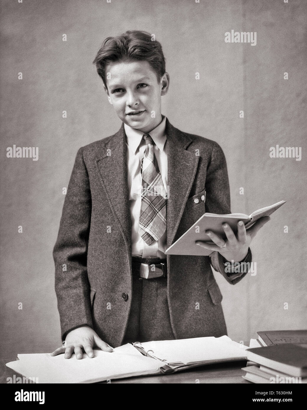 1930s BOY WEARING A SUIT AND TIE STANDING READING FROM NOTEBOOK RECITING AT SCHOOL - s3320 HAR001 HARS EYE CONTACT SCHOOLS SUIT AND TIE GRADE AND AUTHORITY OCCUPATIONS PRIMARY STYLISH K-12 CONFIDENT COOPERATION GRADE SCHOOL GROWTH JUVENILES PRE-TEEN PRE-TEEN BOY RECITING BLACK AND WHITE CAUCASIAN ETHNICITY HAR001 OLD FASHIONED PUBLIC SPEAKING - Stock Image