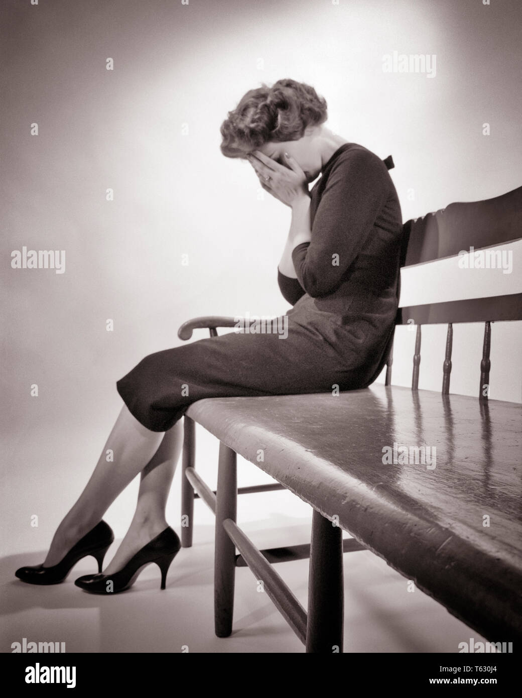 1950s SILHOUETTED DISTRAUGHT WOMAN SITTING ON BENCH CRYING HOLDING HANDS OVER FACE SADNESS DEPRESSION LOSS - s3493 HAR001 HARS LOW ANGLE POWERFUL MOOD SORROW EMBARRASSED GRIEVING CONCEPTUAL GLUM FAILURE MID-ADULT MID-ADULT WOMAN MISERABLE BLACK AND WHITE CAUCASIAN ETHNICITY HAR001 OLD FASHIONED - Stock Image