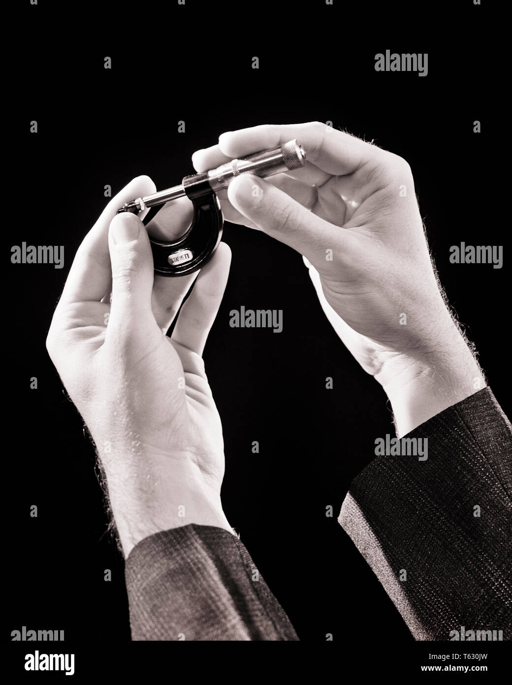 1930s MALE HANDS HOLDING A MICROMETER SCREW GAUGE USED FOR ACCURATE MEASUREMENT OF THICKNESS OF VARIOUS COMPONENT MATERIALS - s4269 HAR001 HARS MID-ADULT MAN PRECISION SCREW SPINDLE YOUNG ADULT MAN ACCURATE BLACK AND WHITE CAUCASIAN ETHNICITY HAR001 OLD FASHIONED - Stock Image