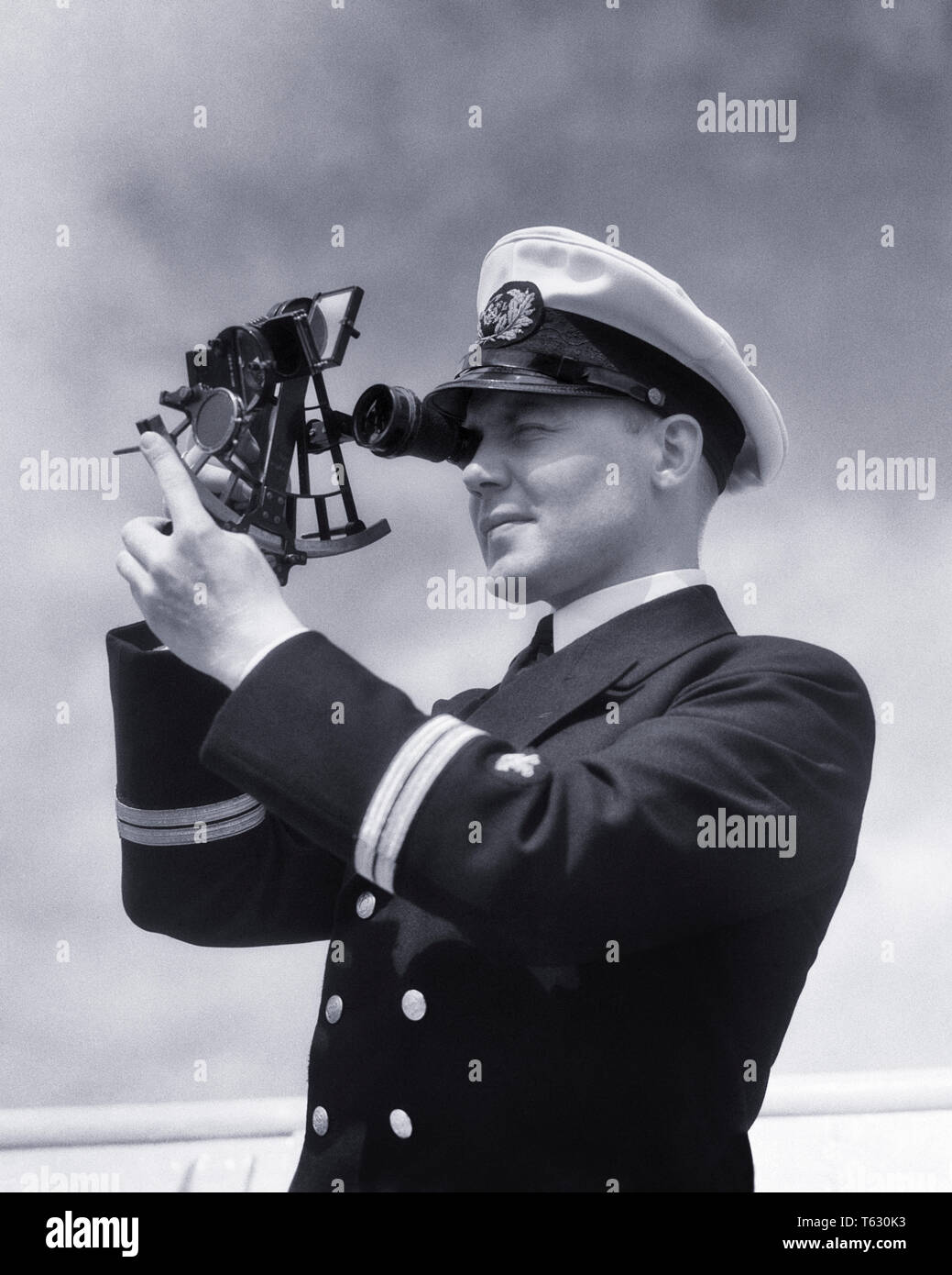 1930s SHIP'S OFFICER USING SEXTANT TO MEASURE ANGULAR DISTANCES BETWEEN OBJECTS TOOL USED IN CELESTIAL NAVIGATION - s5654 HAR001 HARS TRANSPORTATION B&W SEXTANT SKILL OCCUPATION SKILLS ADVENTURE NAVAL CAREERS NAVIGATION DIRECTION OBJECTS OCCUPATIONS USING CONNECTION USED CONCEPTUAL SHIP'S CELESTIAL ANGULAR NAVIGATIONAL PRECISION SHIPPING YOUNG ADULT MAN BLACK AND WHITE CAUCASIAN ETHNICITY HAR001 OLD FASHIONED - Stock Image