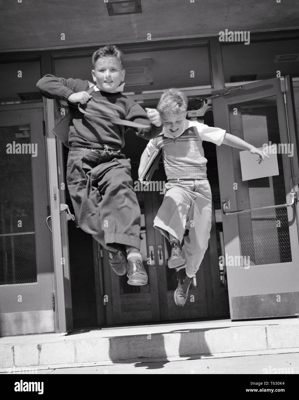 1950s two boys running jumping out the doors of ELEMENTARY school  - s617 HAR001 HARS HEALTHINESS COPY SPACE FRIENDSHIP FULL-LENGTH INSPIRATION MALES RELEASED SIBLINGS CONFIDENCE B&W FREEDOM SCHOOLS GRADE HAPPINESS CHEERFUL ADVENTURE LEAP EXCITEMENT OF THE FREE PRIMARY SIBLING SMILES ESCAPE FRIENDLY JOYFUL K-12 LIBERATED PANORAMIC GRADE SCHOOL GROWTH JUVENILES SCHOOLMATES TOGETHERNESS BLACK AND WHITE CAUCASIAN ETHNICITY CLASSMATES HAR001 OLD FASHIONED - Stock Image