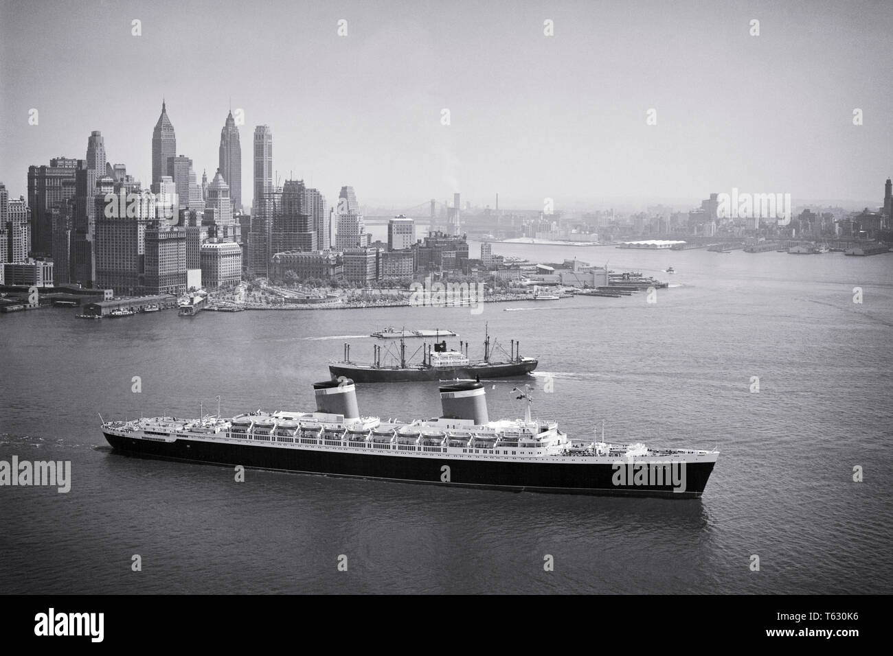 1950s PASSENGER LINER THE SS UNITED STATES HEADS OUT TO SEA FROM NEW YORK HARBOR NYC USA - s636 HAR001 HARS FASTEST MANHATTAN ISLAND BLUE RIBAND GROWTH OCEAN CROSSING OCEAN LINER TRANSATLANTIC AERIAL VIEW BLACK AND WHITE HAR001 HUDSON RIVER OLD FASHIONED VESSEL - Stock Image