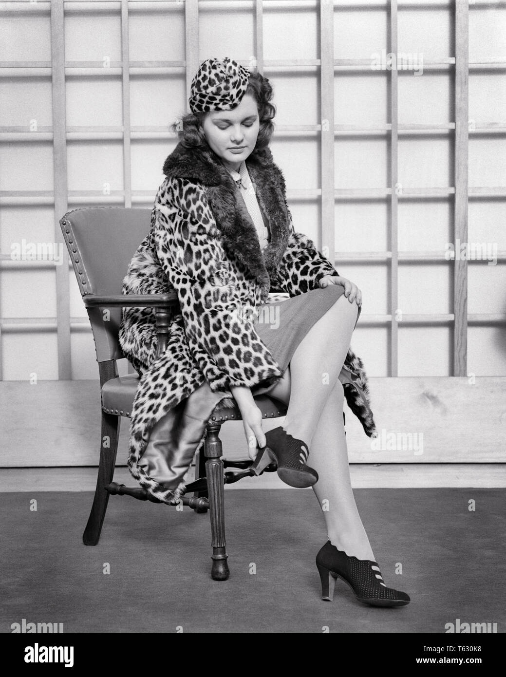 1930 1940s WOMAN WEARING LEOPARD SKIN HAT AND COAT WITH FUR TRIM TRYING ON PAIR OF HIGH HEELED SHOES SITTING IN CHAIR - s7325 HAR001 HARS COPY SPACE FULL-LENGTH HALF-LENGTH LADIES PERSONS SKIN B&W SHOPPER BRUNETTE SHOPPERS DISCOVERY STYLES AND TRYING TRIM HEELED PELT STYLISH LEOPARD SKIN PUTTING ON TRYING ON FASHIONS FURS PAINFUL YOUNG ADULT WOMAN BLACK AND WHITE CAUCASIAN ETHNICITY HAR001 OLD FASHIONED SORE FEET - Stock Image