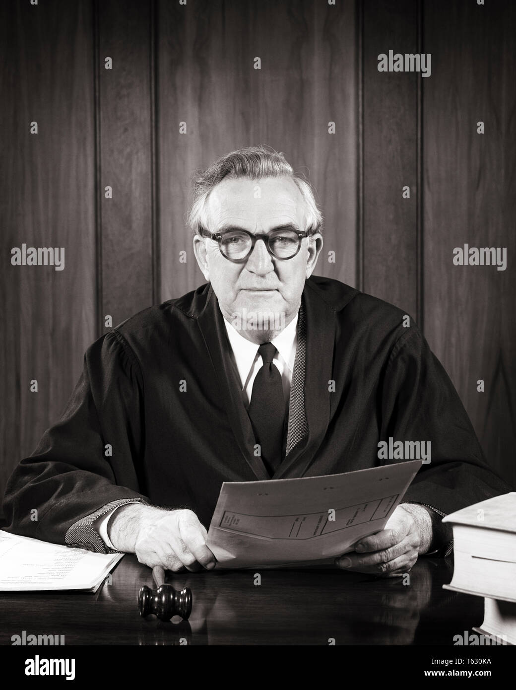 1940s 1950s SERIOUS MAN JUDGE SEATED WEARING ROBE WITH GAVEL AT HAND HOLDING PAPERS  LOOKING AT CAMERA - s7404 HAR001 HARS COMMUNICATION GAVEL LIFESTYLE ELDER JOBS ROBE COPY SPACE HALF-LENGTH PERSONS MALES CONFIDENCE SENIOR MAN SENIOR ADULT EXPRESSIONS MIDDLE-AGED B&W MIDDLE-AGED MAN EYE CONTACT FREEDOM SKILL SUIT AND TIE OCCUPATION SKILLS OLDSTERS OLDSTER ROBES JUDICIAL LAWYERS LEADERSHIP POWERFUL STERN JUDGMENT ATTORNEYS AUTHORITY OCCUPATIONS POLITICS ELDERS CONCEPTUAL ATTORNEY COOPERATION BLACK AND WHITE CAUCASIAN ETHNICITY DIRECT HAR001 OLD FASHIONED - Stock Image