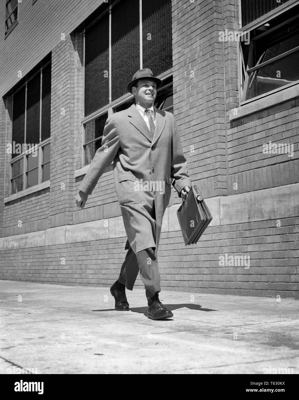 1950s 1960s BUSY SELF CONFIDENT SALESMAN WALKING BRISKLY DOWN CITY STREET WEARING TOP COAT HAT HOLDING BRIEFCASE SMILING - s7416 HAR001 HARS JOY LIFESTYLE SPEED SATISFACTION CELEBRATION HEALTHINESS COPY SPACE FULL-LENGTH PHYSICAL FITNESS PERSONS INSPIRATION CARING MALES CONFIDENCE EXPRESSIONS B&W SELF SUCCESS VISION SUIT AND TIE SELLING HAPPINESS CHEERFUL STRENGTH STRATEGY CUSTOMER SERVICE EXCITEMENT LEADERSHIP LOW ANGLE POWERFUL PROGRESS DIRECTION PRIDE OPPORTUNITY AUTHORITY OCCUPATIONS SMILES ANIMATED CONCEPTUAL JOYFUL STYLISH CONFIDENT MID-ADULT MID-ADULT MAN SALESMEN TOP COAT - Stock Image