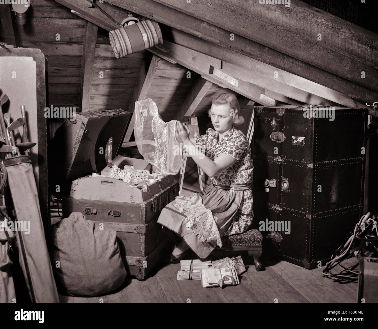 1930s 1940s WOMAN IN CLUTTERED ATTIC WEARING APRON LOOKING THROUGH TRUNK OF OLD CLOTHES LINENS - s7466 HAR001 HARS ATTIC CONNECTION KEEP CLUTTERED LINENS THINGS POSSESSIONS STUFF CLUTTER MEMORIES TRUNKS YOUNG ADULT WOMAN BLACK AND WHITE CAUCASIAN ETHNICITY HAR001 OLD FASHIONED PRESERVE SAVED SOUVENIRS - Stock Image
