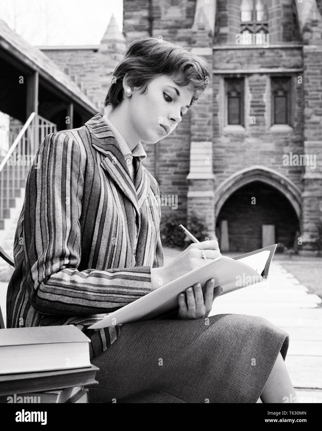 1950s 1960s SERIOUS YOUNG WOMAN COLLEGE COED SITTING ON CAMPUS WRITING IN NOTEBOOK WEARING STRIPED JACKET - s8305 HAR001 HARS FEMALES STRIPED COPY SPACE HALF-LENGTH LADIES PERSONS B&W BRUNETTE GOALS STYLES UNIVERSITIES KNOWLEDGE LOW ANGLE IN ON OPPORTUNITY HIGHER EDUCATION STYLISH COLLEGES COED FASHIONS FOCUSED GROWTH YOUNG ADULT WOMAN BLACK AND WHITE CAUCASIAN ETHNICITY CONCENTRATION HAR001 OLD FASHIONED SHORT HAIR - Stock Image