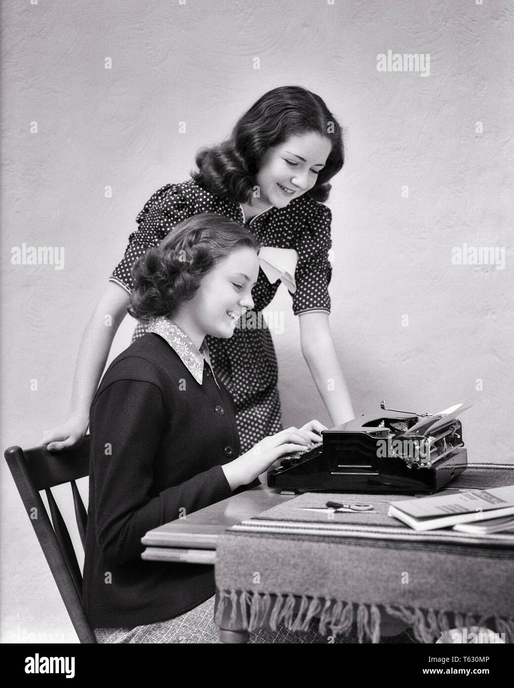 1930s 1940S  TWO TEEN GIRLS WORKING ON SCHOOL PROJECT ONE SEATED AT PORTABLE TYPEWRITER - s8347 HAR001 HARS YOUNG ADULT TEAMWORK PLEASED JOY LIFESTYLE SATISFACTION FEMALES STUDIO SHOT HOME LIFE SEATED COPY SPACE FRIENDSHIP HALF-LENGTH LADIES PERSONS INSPIRATION TEENAGE GIRL SIBLINGS SISTERS PORTABLE B&W BRUNETTE HAPPINESS CHEERFUL TYPING VICTORY UNIVERSITIES HIGH SCHOOL SIBLING SMILES HIGH SCHOOLS HIGHER EDUCATION CONNECTION IMAGINATION JOYFUL STYLISH TEENAGED COLLEGES COOPERATION PROJECT SOLUTIONS YOUNG ADULT WOMAN BLACK AND WHITE CAUCASIAN ETHNICITY HAR001 OLD FASHIONED TYPIST - Stock Image