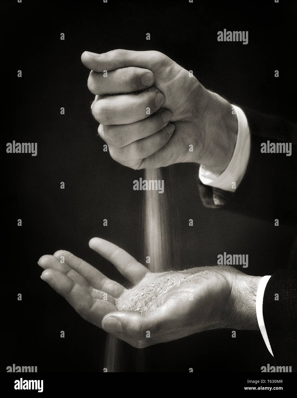 1930s SYMBOLIC HANDS OF A MAN HOLDING LETTING SANDS OF TIME FALL FROM ONE HAND TO THE OTHER - s8433 HAR001 HARS SENIOR MAN SENIOR ADULT MIDDLE-AGED B&W MIDDLE-AGED MAN SUCCESS SUIT AND TIE DREAMS KNOWLEDGE POWERFUL A LETTING OF OPPORTUNITY THE TO SANDS OF TIME CONCEPT CONCEPTUAL CLOSE-UP ELDERLY MAN SYMBOLIC CONCEPTS IDEAS MID-ADULT MID-ADULT MAN YOUNG ADULT MAN BLACK AND WHITE CAUCASIAN ETHNICITY HAR001 OLD FASHIONED REPRESENTATION - Stock Image