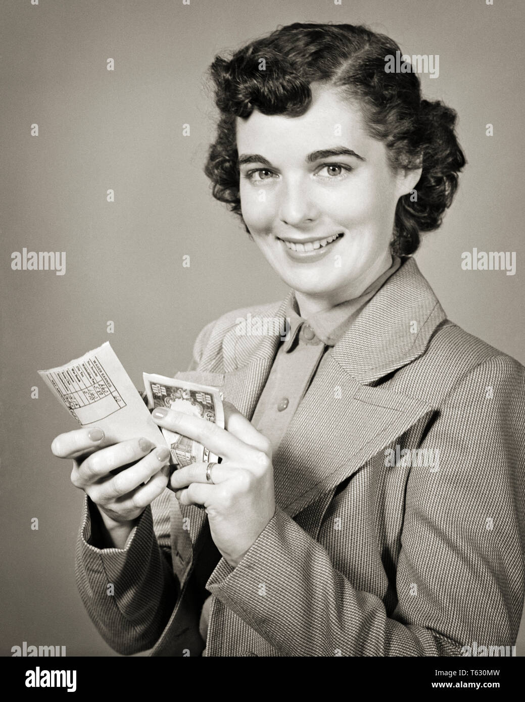 1940s 1950s SMILING BRUNETTE WOMAN LOOKING AT CAMERA OPENING PAYCHECK ENVELOPE AND HOLDING THE CASH - s8493 HAR001 HARS BRUNETTE FREEDOM SKILL TEMPTATION DREAMS OCCUPATION HAPPINESS SKILLS PAYCHECK CHEERFUL STRENGTH PAY AND EXCITEMENT PRIDE THE OCCUPATIONS SMILES JOYFUL STYLISH COMPENSATION EMPLOYEE YOUNG ADULT WOMAN BLACK AND WHITE CAUCASIAN ETHNICITY HAR001 OLD FASHIONED - Stock Image