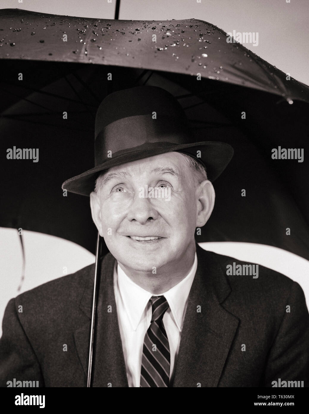 1950s 1960s ELDERLY MAN UNDER UMBRELLA LOOKING UP AT RAIN DROPS - s8706 HAR001 HARS UP FORECAST ELDERS CONCEPTUAL DROPS LOOKING UP BLACK AND WHITE CAUCASIAN ETHNICITY HAR001 METEOROLOGY OLD FASHIONED PRECIPITATION - Stock Image