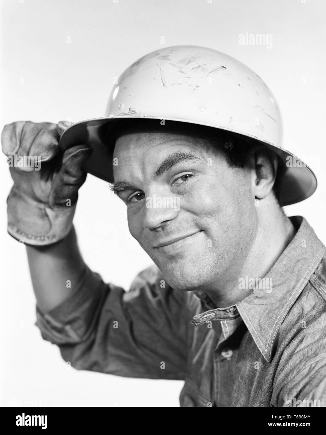 1960s CONSTRUCTION WORKER TIPPING HIS HARD HAT LOOKING AT CAMERA - s8756 HAR001 HARS B&W EYE CONTACT BLUE COLLAR SKILL OCCUPATION SKILLS HEAD AND SHOULDERS CHEERFUL HIS PROTECTION HARD HAT LABOR EMPLOYMENT OCCUPATIONS SMILES JOYFUL EMPLOYEE COOPERATION MID-ADULT MID-ADULT MAN TIPPING BLACK AND WHITE CAUCASIAN ETHNICITY HAR001 LABORING OLD FASHIONED - Stock Image