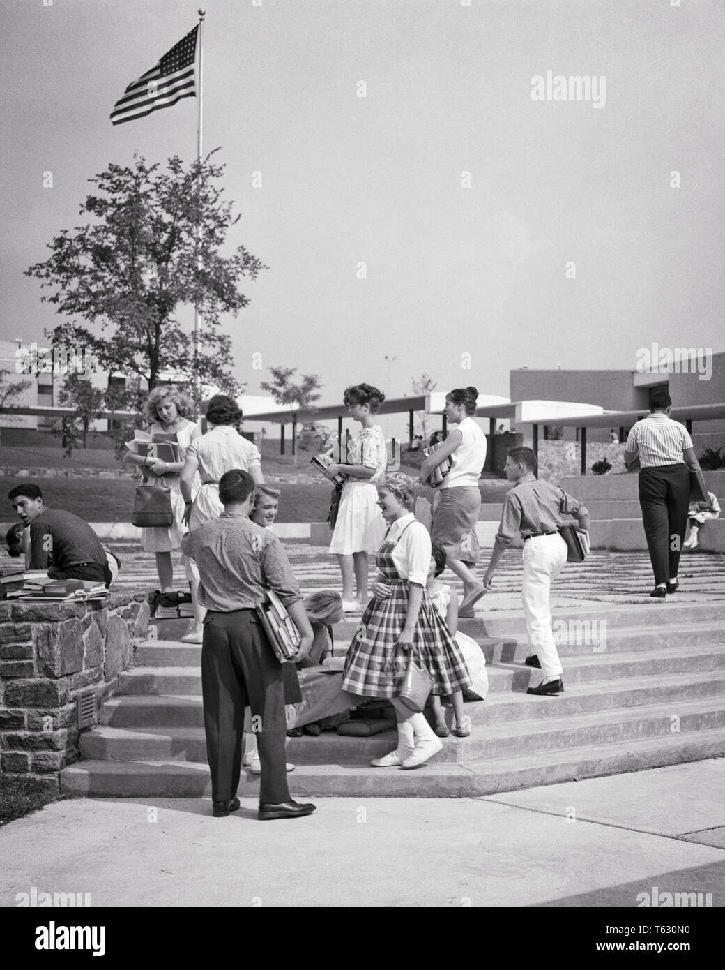 1960s 1950s TEENAGE STUDENTS ON STEPS OUTSIDE A   HIGH SCHOOL BUILDING - s8778 HAR001 HARS ARCHITECTURE FEMALES HEALTHINESS COPY SPACE FRIENDSHIP FULL-LENGTH PERSONS MALES TEENAGE GIRL TEENAGE BOY BUILDINGS B&W HAPPINESS PROPERTY STYLES NETWORKING EXCITEMENT EXTERIOR HIGH SCHOOL HIGH SCHOOLS REAL ESTATE CONNECTION STRUCTURES STYLISH TEENAGED EDIFICE FASHIONS GROWTH JUVENILES TOGETHERNESS BLACK AND WHITE CAUCASIAN ETHNICITY HAR001 OLD FASHIONED - Stock Image