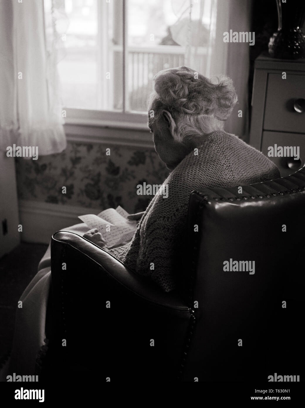 1960s ANONYMOUS ELDERLY WOMAN SITTING IN CHAIR BY SUNLIT WINDOW  READING A HANDWRITTEN LETTER - s8784 HAR001 HARS HOME LIFE COPY SPACE FRIENDSHIP HALF-LENGTH LADIES PERSONS INSPIRATION CARING SERENITY SENIOR ADULT B&W SADNESS SENIOR WOMAN DREAMS OLDSTERS HIGH ANGLE OLDSTER AGING POWERFUL REAR VIEW FEELING MOOD SHAWL TIMELESS ELDERS CONNECTION NURSING HOME CONCEPTUAL FORGOTTEN HANDWRITTEN ANONYMOUS REMEMBERED ASSISTED LIVING BACK VIEW ELDERLY WOMAN EMOTION EMOTIONAL EMOTIONS FRAIL LONGEVITY BLACK AND WHITE CAUCASIAN ETHNICITY HAR001 OLD FASHIONED - Stock Image