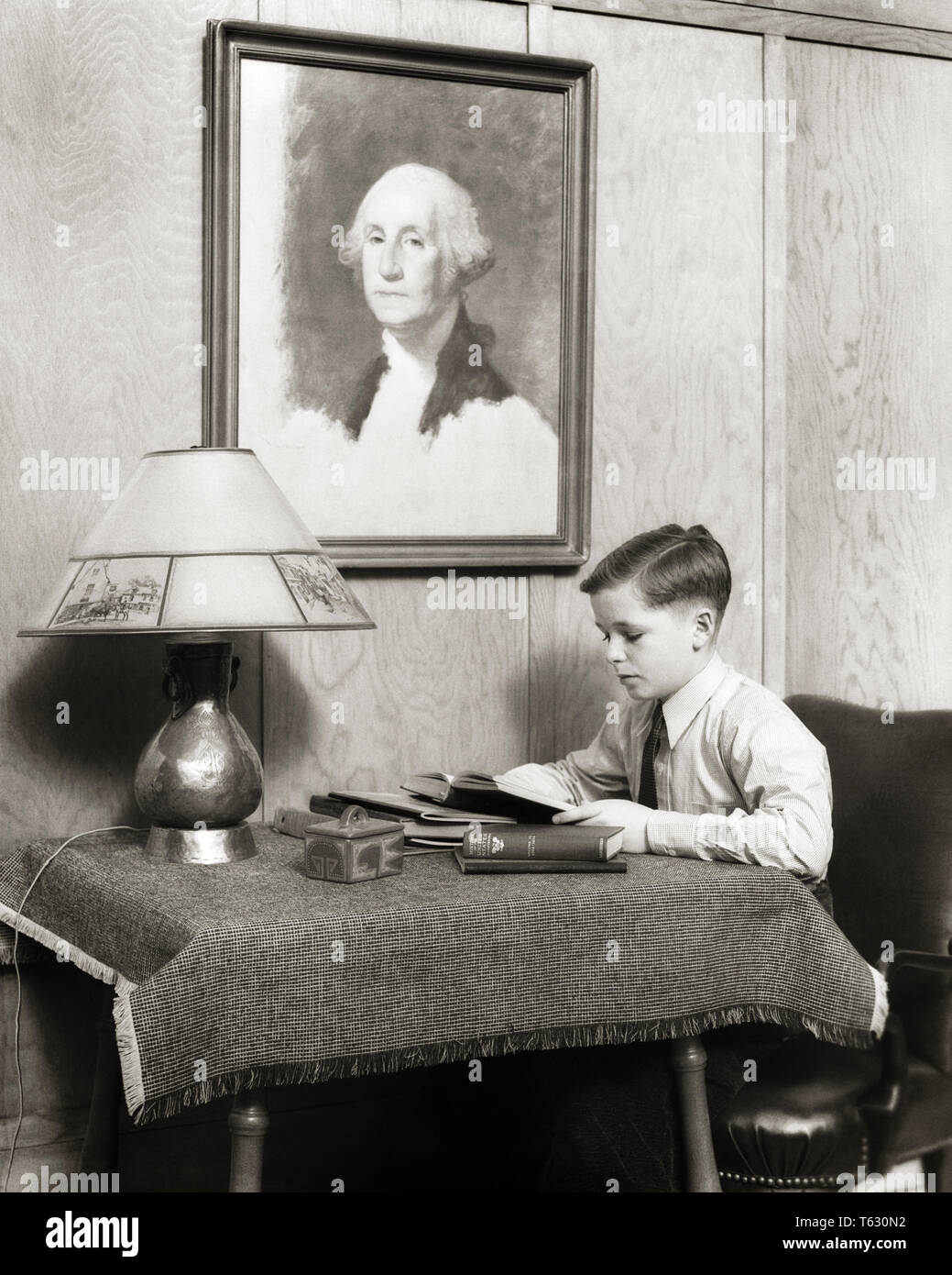 1930s STUDIOUS BOY DOING HOMEWORK SITTING READING AT TABLE UNDER PORTRAIT OF GEORGE WASHINGTON - s8901 HAR001 HARS JUVENILES STUDIOUS TABLE LAMP BLACK AND WHITE CAUCASIAN ETHNICITY HAR001 OLD FASHIONED - Stock Image