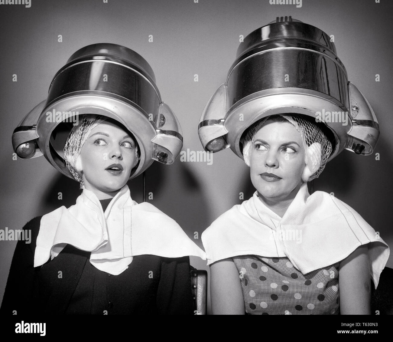1950s TWO WOMEN SITTING UNDER BEAUTY SALON HAIR DRYERS WEARING HAIRNETS TOWELS TALKING GOSSIP  - s8918 DEB001 HARS EXCITEMENT HAIRSTYLE KNOWLEDGE FEMININE HOUSEWIVES GOSSIPS DRYERS GIRLFRIENDS DEB001 HAIR NETS MID-ADULT MID-ADULT WOMAN TOGETHERNESS YOUNG ADULT WOMAN BLACK AND WHITE CAUCASIAN ETHNICITY OLD FASHIONED TWO WOMEN - Stock Image