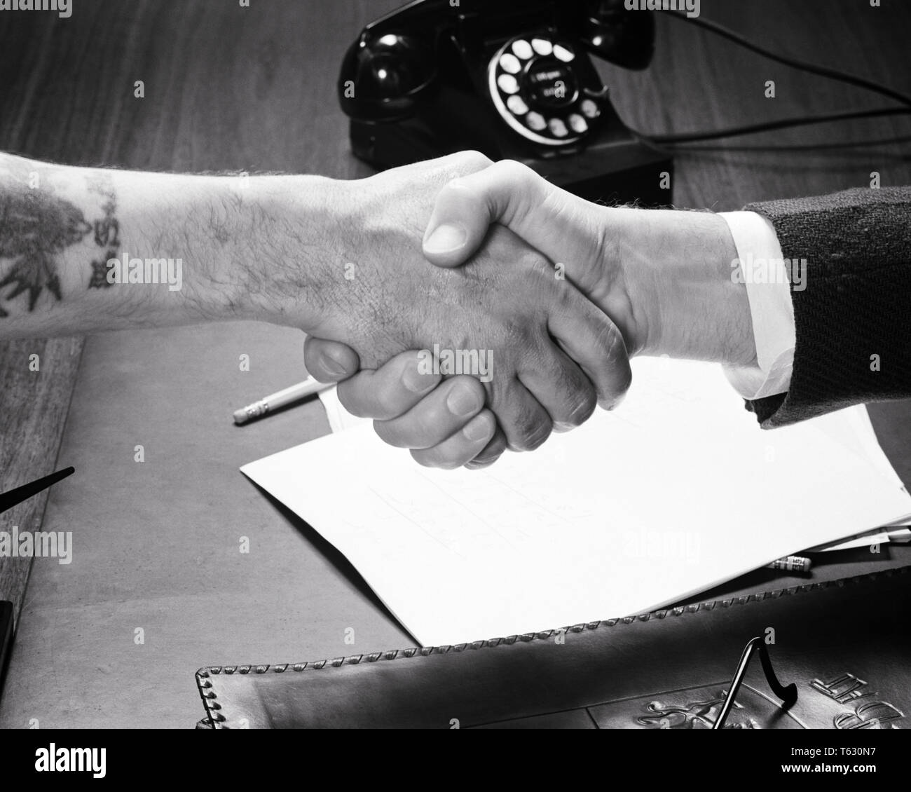 1940s 1950s BUSINESSMAN SHAKING HANDS WITH WORKMAN MANUAL LABORER OVER OFFICE DESK WITH TELEPHONE - s9462 HAR001 HARS PERSONS INSPIRATION MALES MANAGEMENT B&W GOALS SUCCESS SKILL CUFF OCCUPATION SKILLS AGREE HIGH ANGLE MANUAL STRENGTH STRATEGY AGREEMENT LEADERSHIP PROGRESS LABOR OPPORTUNITY EMPLOYMENT OCCUPATIONS SHAKING HANDS CONNECTION CONCEPTUAL SUPPORT EMPLOYEE TATOO COOPERATION GROWTH IDEAS SOLUTIONS TOGETHERNESS BLACK AND WHITE CAUCASIAN ETHNICITY HANDS ONLY HAR001 LABORER LABORING OLD FASHIONED - Stock Image