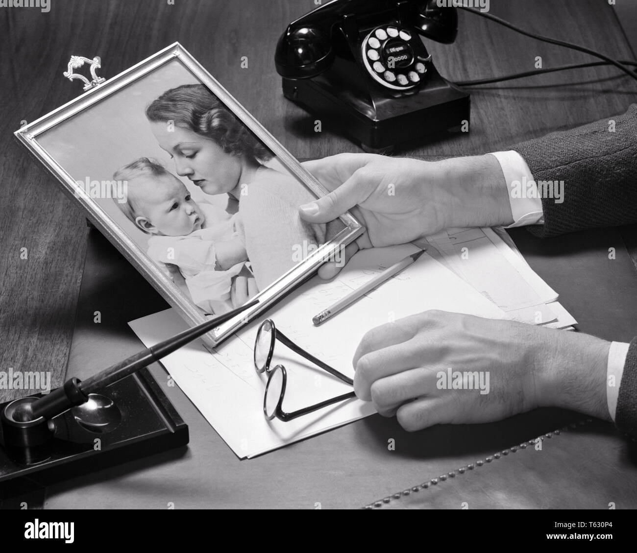 1940s BUSINESSMAN'S HANDS HOLDING A FRAMED PHOTO OF HIS WIFE AND  BABY ON HIS DESK WITH PHONE PEN PAPER AND EYEGLASSES - s9495 HAR001 HARS PAIR MOTHERS OLD TIME NOSTALGIA OLD FASHION 1 PHOTOGRAPH JUVENILE YOUNG ADULT FAMILIES JOY LIFESTYLE SATISFACTION FEMALES MARRIED STUDIO SHOT SPOUSE HUSBANDS HOME LIFE COPY SPACE LADIES PERSONS CARING MALES EYEGLASSES B&W PARTNER HIGH ANGLE HIS AND PRIDE A OF ON OCCUPATIONS CONCEPTUAL FRAMED JUVENILES MID-ADULT MID-ADULT MAN MOMS TOGETHERNESS WIVES YOUNG ADULT WOMAN BABY GIRL BLACK AND WHITE CAUCASIAN ETHNICITY HANDS ONLY HAR001 OLD FASHIONED - Stock Image