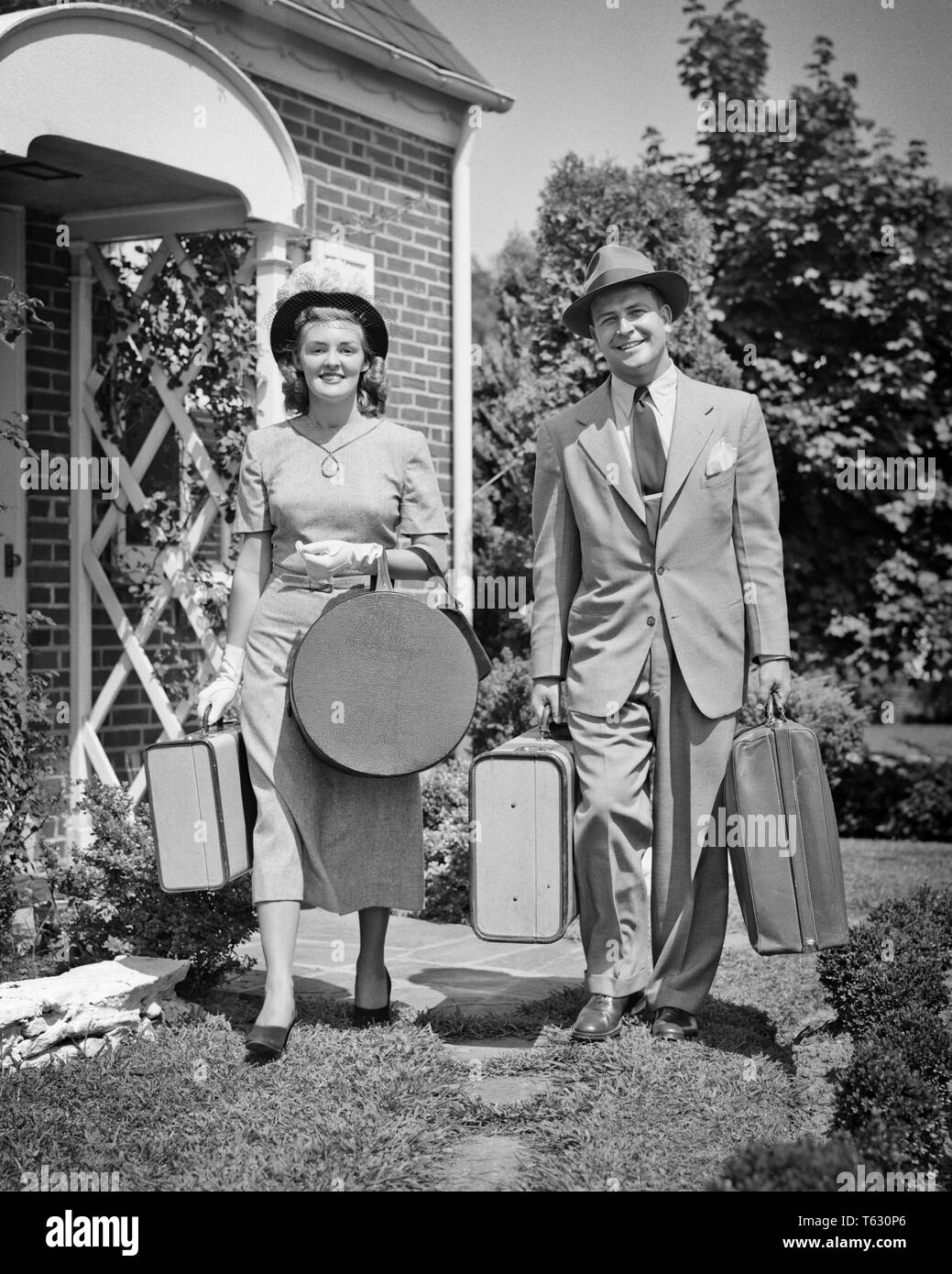 1940s 1950s COUPLE MAN WOMAN LEAVING HOUSE LOOKING AT CAMERA BEGINNING A TRIP CARRYING LUGGAGE SUITCASES AND HATBOX - s985 HAR001 HARS JOY LIFESTYLE FEMALES HOUSES MARRIED SPOUSE HUSBANDS HEALTHINESS HOME LIFE COPY SPACE FRIENDSHIP FULL-LENGTH LADIES PERSONS RESIDENTIAL MALES BUILDINGS CONFIDENCE B&W EYE CONTACT TIME OFF SUIT AND TIE HAPPINESS CHEERFUL ADVENTURE LEISURE TRIP GETAWAY DIRECTION HOLIDAYS HOMES SMILES JOYFUL RESIDENCE STYLISH HATBOX WHITE GLOVES COOPERATION HAT HATS MID-ADULT MID-ADULT MAN MID-ADULT WOMAN TOGETHERNESS VACATIONS WIVES BEGINNING BLACK AND WHITE CAUCASIAN ETHNICITY - Stock Image