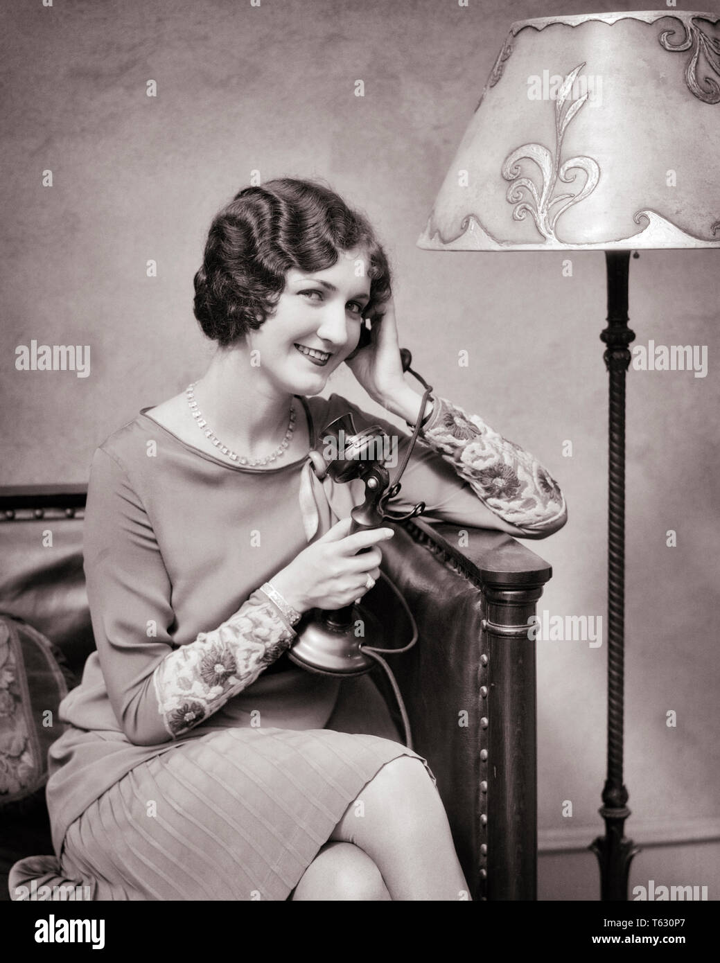 1920s SMILING WELL DRESSED WOMAN TALKING ON CANDLESTICK TELEPHONE - t2306 HAR001 HARS HALF-LENGTH LADIES PERSONS B&W CANDLESTICK BRUNETTE PRETTY HAPPINESS CHEERFUL STYLES HAIRSTYLE LAMPSHADE PHONES SMILES FINGER WAVES CONNECTION FLOOR LAMP TELEPHONES JOYFUL STYLISH FASHIONS YOUNG ADULT WOMAN BLACK AND WHITE CAUCASIAN ETHNICITY HAR001 OLD FASHIONED - Stock Image