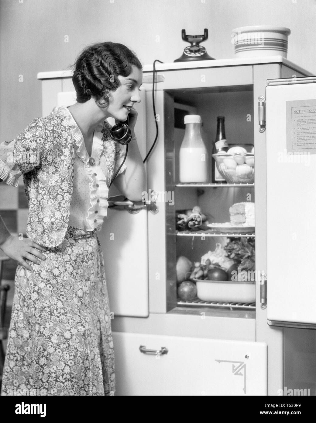 1920s SMILING WOMAN SPEAKING ON TELEPHONE LOOKING INTO THE KITCHEN ICEBOX REFRIGERATOR PLACING ORDER WITH GROCER - t2987 HAR001 HARS LIFESTYLE FEMALES HOME LIFE COMMUNICATING COPY SPACE HALF-LENGTH LADIES PERSONS ORDER B&W BRUNETTE GOALS HOMEMAKER FRESH HOMEMAKERS CHEERFUL DISCOVERY STYLES CUSTOMER SERVICE GROCER HAIRSTYLE HOUSEWIVES PHONES SMILES FINGER WAVES TELEPHONES JOYFUL PRODUCE STYLING STYLISH ICEBOX COOPERATION FASHIONS MARCEL ORDERING YOUNG ADULT WOMAN BLACK AND WHITE CAUCASIAN ETHNICITY HAR001 OLD FASHIONED PLACING - Stock Image