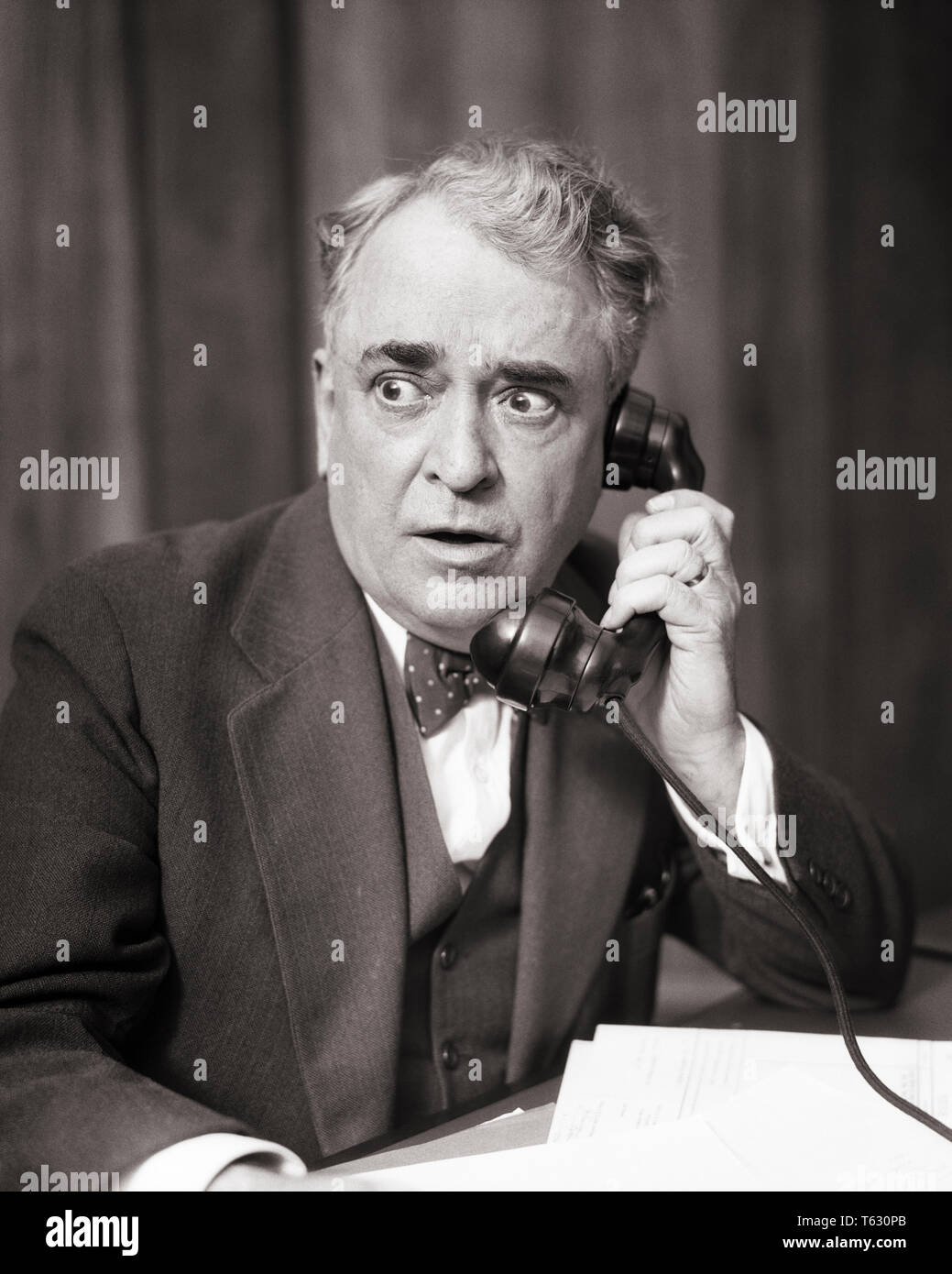 1930s BUSINESS MAN LISTENING ON TELEPHONE WITH ALARMED SHOCKED WORRIED FACIAL EXPRESSION - t3549 HAR001 HARS NOSTALGIA OLD FASHION 1 FACIAL ANGER COMMUNICATION SHOCK SHOCKED TROUBLE PROBLEM LIFESTYLE ELDER JOBS MANAGER COPY SPACE HALF-LENGTH PERSONS THOUGHTFUL MALES RISK SENIOR MAN EXECUTIVES SENIOR ADULT B&W SADNESS OCCUPATION SELLING OLDSTERS OLDSTER POLITICIAN STUNNED CONCERN OCCUPATIONS PHONES POLITICS ELDERS BOSSES TELEPHONES ATTORNEY FOCUSED INTENSE MANAGERS SALESMEN BLACK AND WHITE CAUCASIAN ETHNICITY HAR001 INTENT OLD FASHIONED - Stock Image