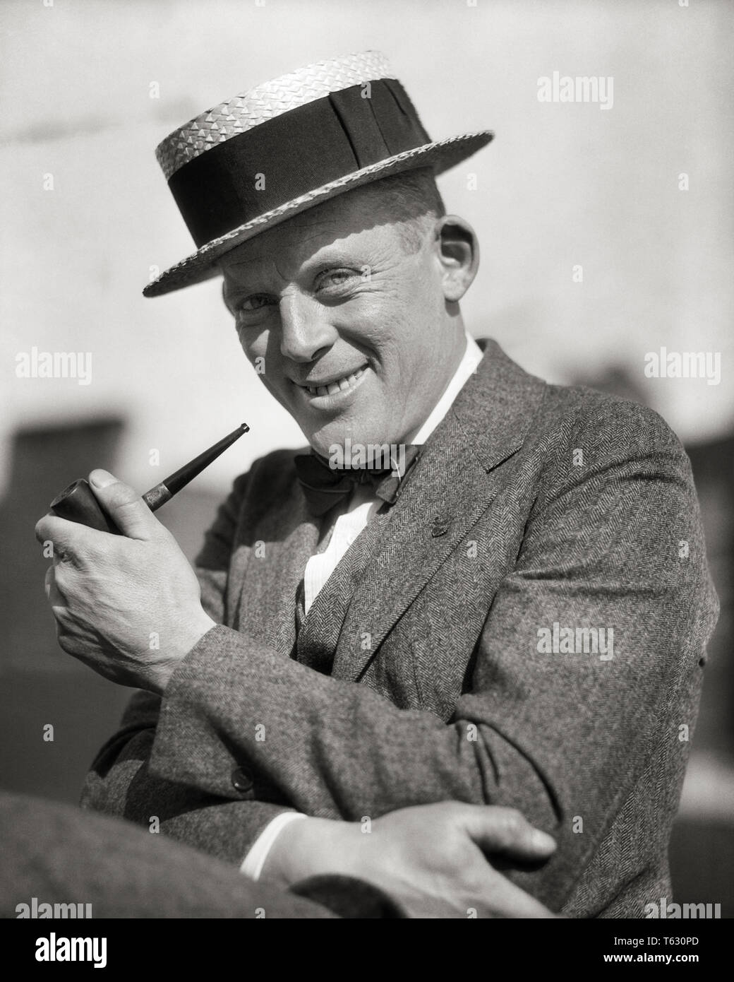 4a4c5e094506ab 1920s PORTRAIT SMILING MAN SMOKING A PIPE WEARING A STRAW BOATER STYLE HAT  SUIT BOW TIE