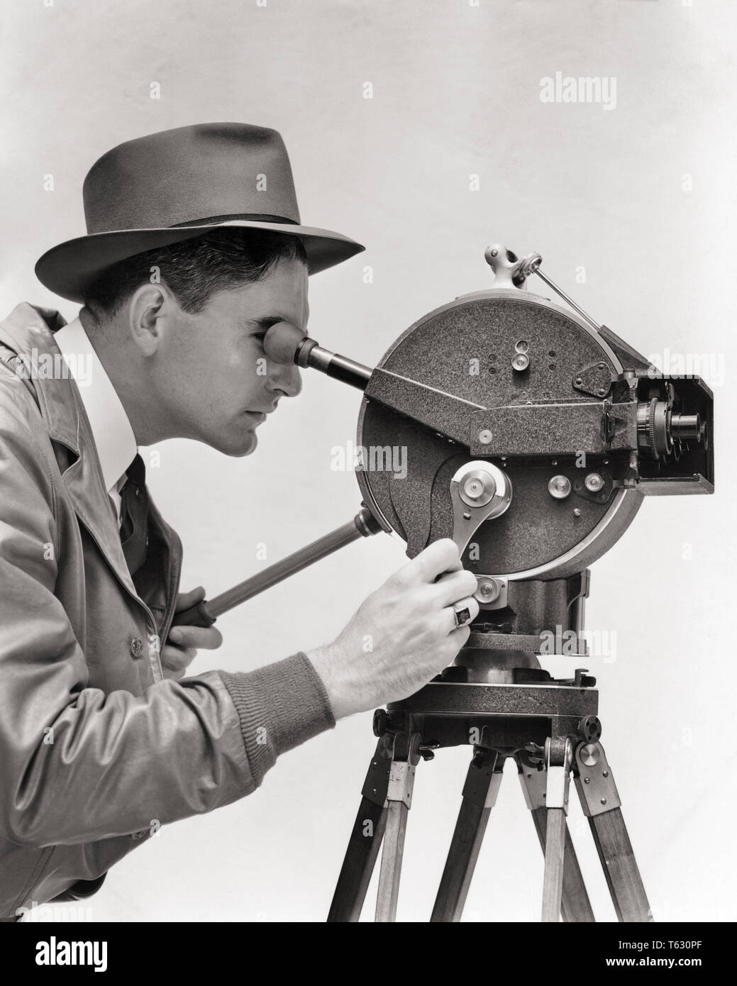 1930s PORTRAIT PROFILE MAN CINEMATOGRAPHER OPERATING AKELEY HAND CRANK PORTABLE 35 MM FILM MOVIE CAMERA MOUNTED ON TRIPOD - u137 HAR001 HARS HISTORY JOBS STUDIO SHOT RURAL FILMING COPY SPACE HALF-LENGTH PHYSICAL FITNESS PERSONS INSPIRATION MALES CAMERAMAN ENTERTAINMENT CONFIDENCE PORTABLE TRIPOD B&W SUCCESS PERFORMING ARTS VISION SKILL OCCUPATION HAPPINESS SKILLS OPERATING ADVENTURE AND EXCITEMENT KNOWLEDGE DIRECTION PHOTOGRAPHING BY ON OPPORTUNITY THE OCCUPATIONS USED CONCEPTUAL IMAGINATION STYLISH US ARMY CREATIVITY DIRECTORS IDEAS MID-ADULT MID-ADULT MAN MOUNTED BLACK AND WHITE CARL AKELEY - Stock Image