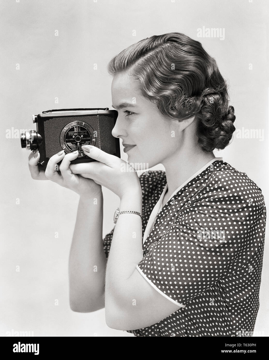 1930s PROFILE OF YOUNG WOMAN USING A 8MM HOME MOVIE CAMERA - u399 HAR001 HARS RECORDING B&W SKILL ACTIVITY AMUSEMENT DISCOVERY HOBBY LEISURE INTEREST HOBBIES KNOWLEDGE RECREATION PASTIME PHOTOGRAPHING PLEASURE OF OPPORTUNITY USING CONCEPTUAL STYLISH 8MM CREATIVITY RELAXATION YOUNG ADULT WOMAN AMATEUR BLACK AND WHITE CAUCASIAN ETHNICITY ENJOYMENT HAR001 OLD FASHIONED - Stock Image