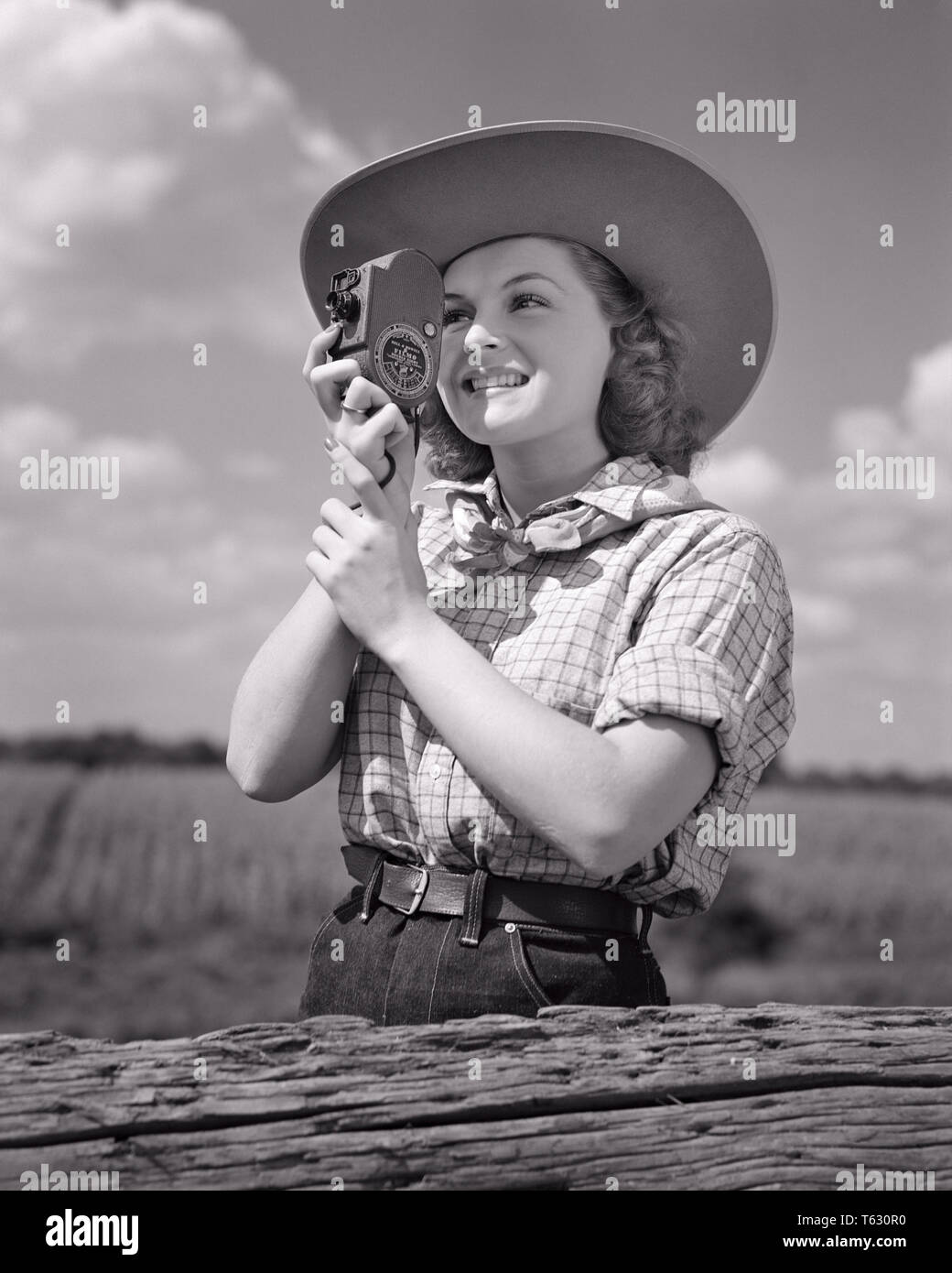 1940s SMILING YOUNG WOMAN IN COWBOY HAT AND WESTERN CLOTHES PHOTOGRAPHING USING HAND HELD 8MM HOME MOVIE CAMERA - u532 HAR001 HARS HOBBY LEISURE INTEREST AND EXCITEMENT HOBBIES KNOWLEDGE RECREATION PASTIME PHOTOGRAPHING PLEASURE IN SMILES USING CONCEPTUAL JOYFUL STYLISH 8MM HAND HELD RELAXATION YOUNG ADULT WOMAN AMATEUR BLACK AND WHITE CAUCASIAN ETHNICITY ENJOYMENT HAR001 OLD FASHIONED - Stock Image