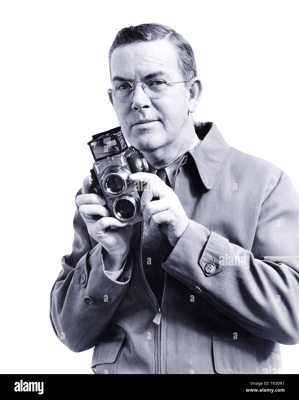 1930s H ARMSTRONG ROBERTS AGE 55 YEARS PROFESSIONAL PHOTOGRAPHER LOOKING AT CAMERA HOLDING TWIN LENS REFLEX ROLL FILM CAMERA  - u420 HAR001 HARS HALF-LENGTH PERSONS INSPIRATION MALES PROFESSION CONFIDENCE EXPRESSIONS MIDDLE-AGED B&W MIDDLE-AGED MAN EYE CONTACT VISION SKILL OCCUPATION SKILLS CHEERFUL ADVENTURE LEISURE CAREERS RECREATION PRIDE PHOTOGRAPHING AUTHORITY OCCUPATIONS SMILES CONCEPTUAL H ARMSTRONG ROBERTS JOYFUL STYLISH REFLEX ROLL FILM CREATIVITY RELAXATION TWIN LENS BLACK AND WHITE CAUCASIAN ETHNICITY HAR001 OLD FASHIONED - Stock Image
