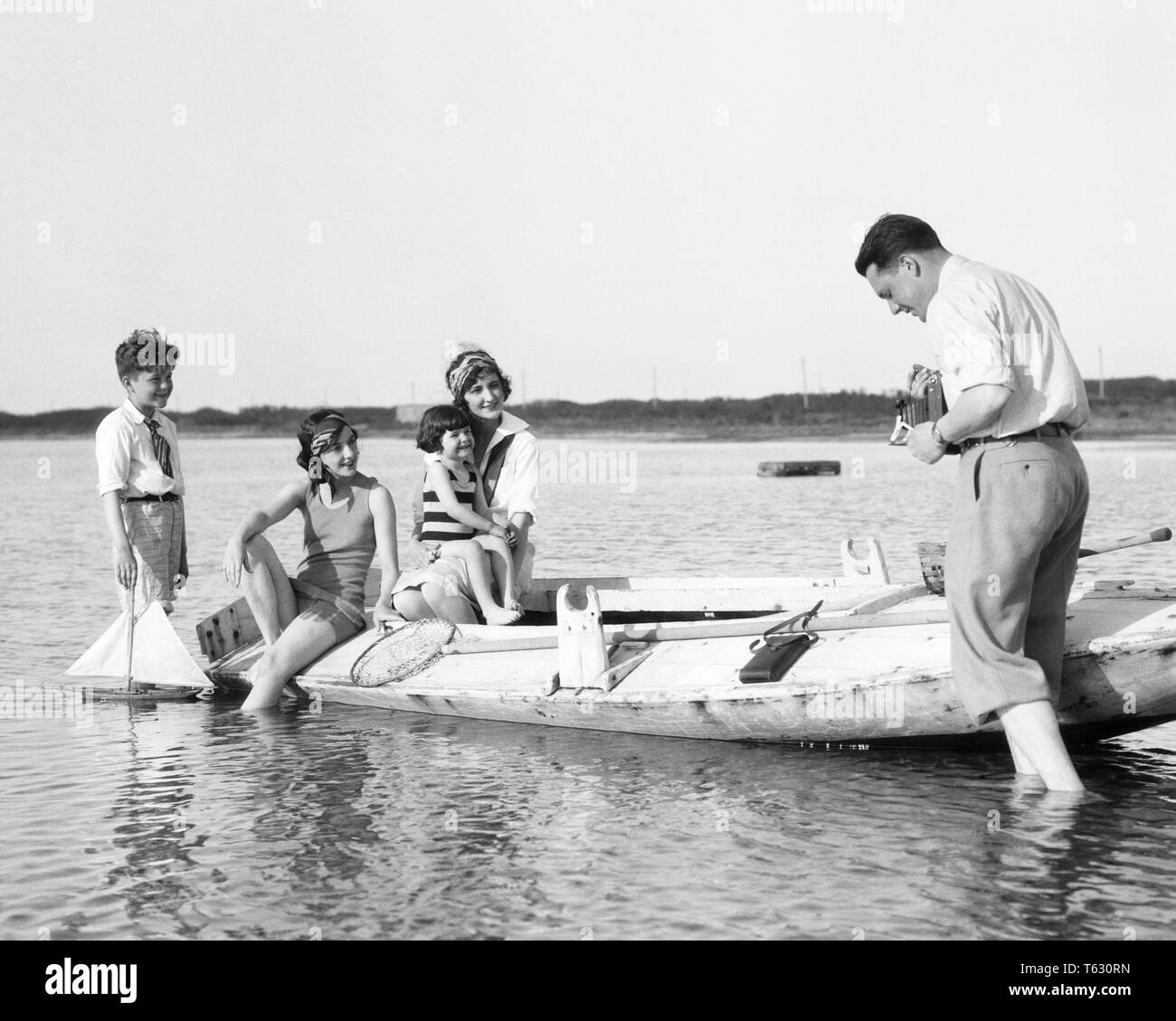 1920s FATHER WITH FOLDING KODAK CAMERA PHOTOGRAPHING WIFE SON DAUGHTER AND AUNT ON WOODEN DUCK BOAT BARNEGAT BAY NEW JERSEY USA - u840 HAR001 HARS MOM WOODEN NOSTALGIC PAIR BEAUTY MOTHERS OLD TIME NOSTALGIA BROTHER OLD FASHION SISTER 1 JUVENILE COMMUNICATION YOUNG ADULT TEAMWORK VACATION RELAXING SONS PLEASED FAMILIES JOY LIFESTYLE FIVE CELEBRATION FEMALES MARRIED 5 BROTHERS RURAL SPOUSE HUSBANDS COPY SPACE FULL-LENGTH LADIES DAUGHTERS PERSONS MALES FOLDING SIBLINGS SISTERS FATHERS B&W PARTNER TIME OFF SKILL ACTIVITY AMUSEMENT HAPPINESS CHEERFUL HOBBY TRIP INTEREST AND GETAWAY DADS EXCITEMENT - Stock Image