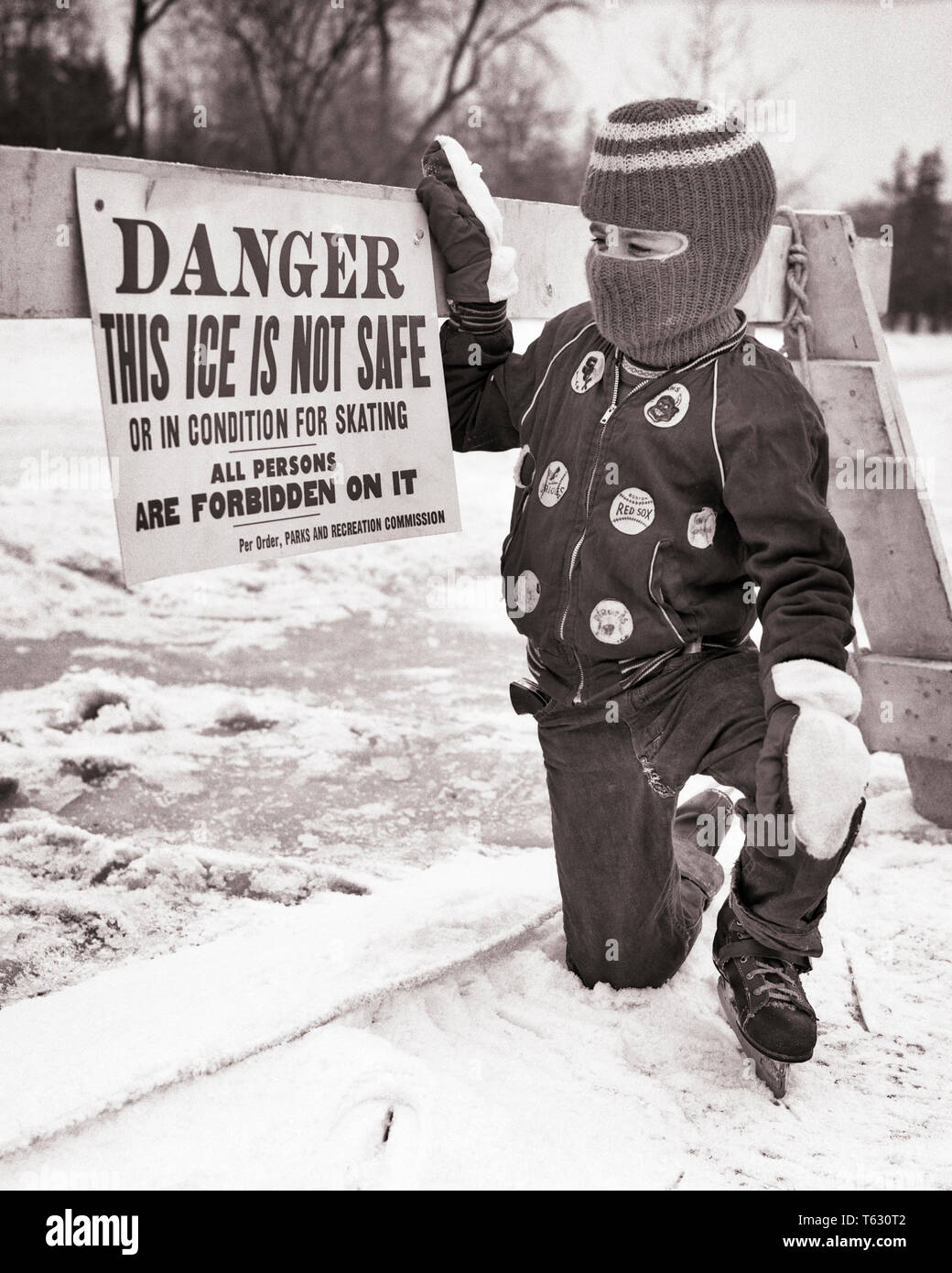 1950s 1960s BOY WEARING ICE SKATES SKI MASK MITTENS WINTER JACKET READING DANGER ICE IS NOT SAFE SIGN - w4949 HAR001 HARS RISK MITTENS ATHLETIC B&W TEMPTATION DISASTER DANGEROUS PROTECTION CHOICE WARNING CONCEPTUAL SKI MASK ICE SKATING JUVENILES NOT SAFE BLACK AND WHITE CAUCASIAN ETHNICITY HAR001 ICE SKATES OLD FASHIONED - Stock Image