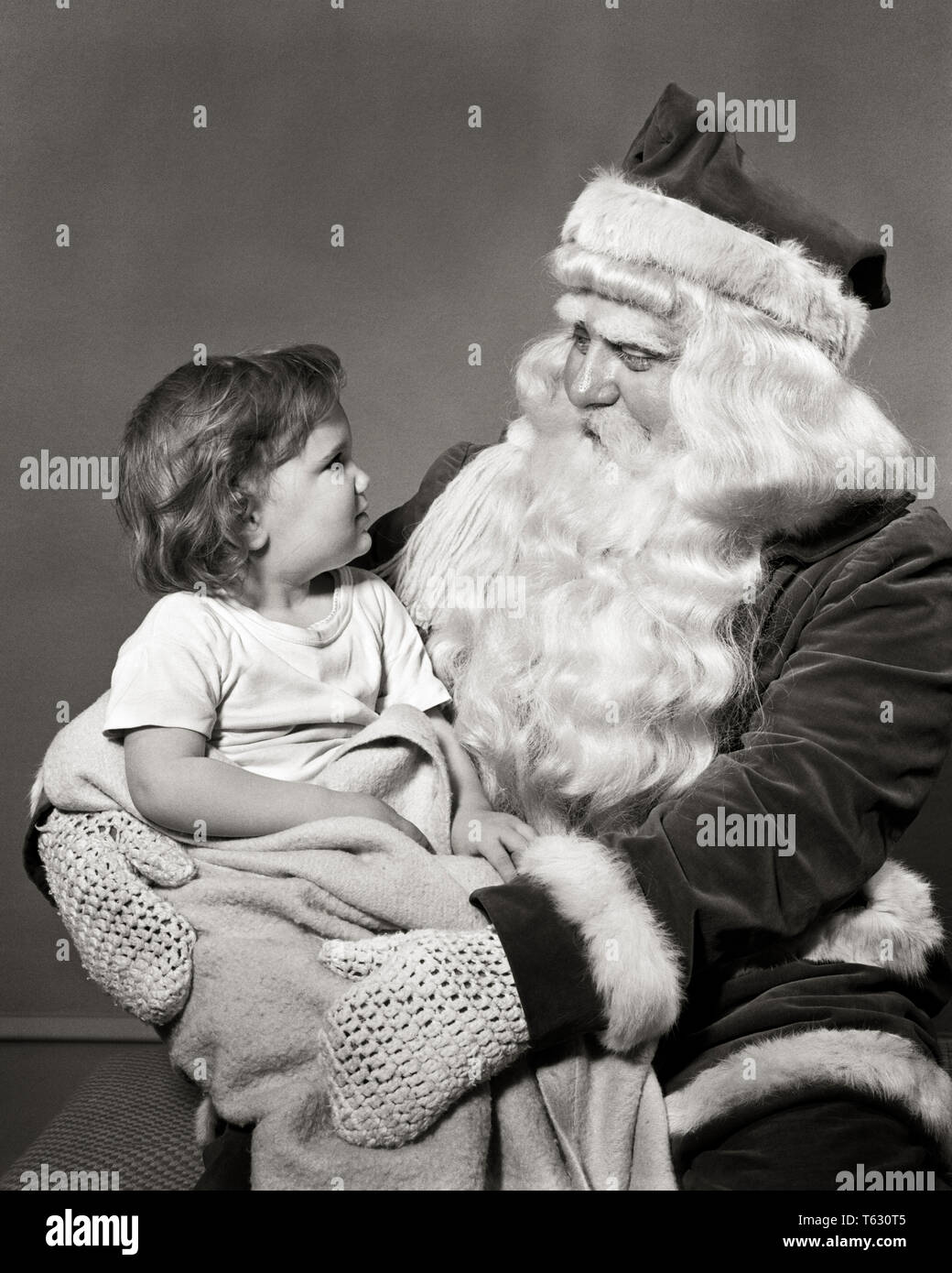1940s 1950s LITTLE GIRL SITTING ON SANTA CLAUS LAP SMILING AT EACH OTHER  - x4919 HAR001 HARS FACIAL COMMUNICATION PLEASED JOY LIFESTYLE FEMALES STUDIO SHOT CLAUS COPY SPACE HALF-LENGTH PERSONS MALES SYMBOLS SENIOR MAN SAINT EXPRESSIONS B&W LAP CHEERFUL EXCITEMENT SANTA CLAUS FACIAL HAIR HOLIDAYS OCCUPATIONS SMILES DECEMBER CONCEPT CONCEPTUAL JOYFUL KRIS KRINGLE ST. NICK STYLISH ELDERLY MAN SYMBOLIC CONCEPTS FATHER CHRISTMAS JOLLY JUVENILES NICHOLAS BLACK AND WHITE CAUCASIAN ETHNICITY HAR001 OLD FASHIONED REPRESENTATION UNCERTAIN - Stock Image