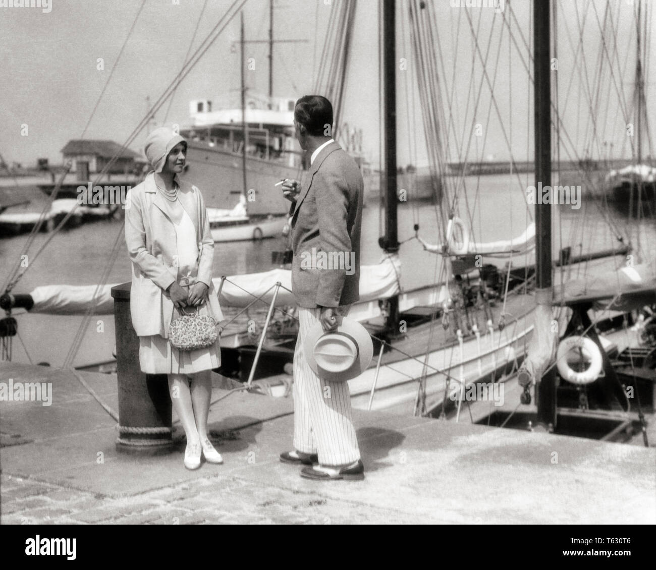1920s WELL DRESSED STYLISH COUPLE STANDING TALKING TOGETHER MAN  SMOKING CIGARETTE YACHT MARINA DEAUVILLE FRANCE  - y1064 HAR001 HARS OLD FASHION 1 STYLE FRANCE VACATION YACHT JOY LIFESTYLE HISTORY CELEBRATION FEMALES MARRIED SPOUSE HUSBANDS HEALTHINESS LUXURY COPY SPACE FRIENDSHIP FULL-LENGTH LADIES PERSONS MALES B&W PARTNER SUMMERTIME RESORT TIME OFF DREAMS HAPPINESS ADVENTURE DISCOVERY STYLES TRIP GETAWAY RECREATION SEASIDE CLOCHE WELL DRESSED HOLIDAYS REGION NORTHWESTERN CONCEPTUAL SPORT JACKET SAIL BOAT STYLISH NORMANDY FASHIONS MID-ADULT MID-ADULT MAN MID-ADULT WOMAN PANAMA HAT - Stock Image