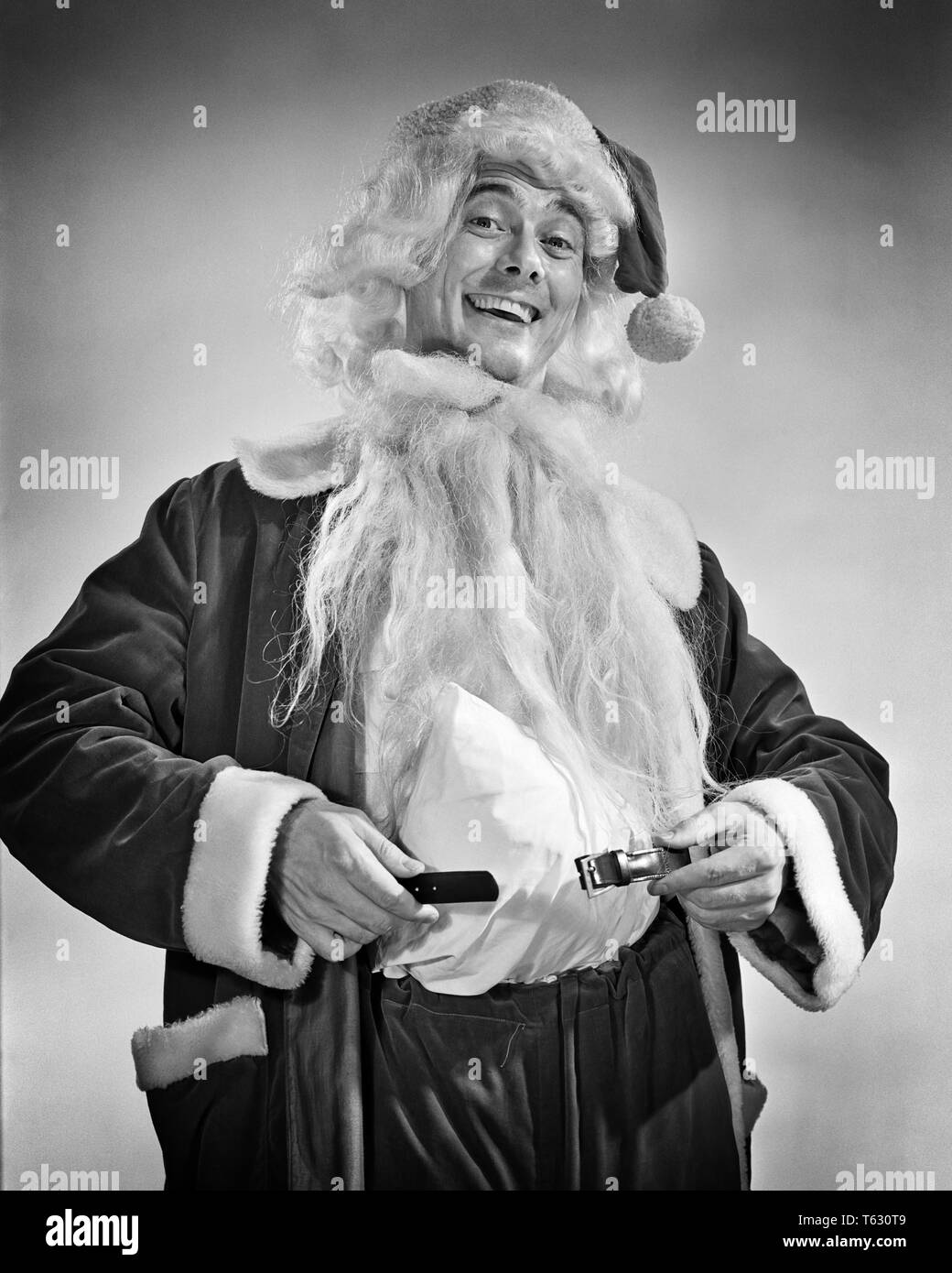 1950s SMILING MAN DRESSING UP IN SANTA COSTUME HOLDING BELT AROUND PADDED STOMACH  - x2535 RCH001 HARS BEARD 1 PEACE PLEASED JOY LIFESTYLE BELT CELEBRATION STUDIO SHOT GROWNUP CLAUS HOME LIFE COPY SPACE HALF-LENGTH ICON INSPIRATION WISE CHARACTER MALES SAINT B&W EYE CONTACT ICONS HAIRS OCCUPATION HAPPINESS CHEERFUL STOMACH WISDOM SYMBOLISM WHISKER CHARACTERS SPECIAL SANTA CLAUS OCCASION PEOPLE CHARACTERS SAINT NICHOLAS SAINT NICK SPECIAL OCCASION RED SUIT OLD SAINT NICK ROTUND UP FACIAL HAIR HOLIDAYS OCCUPATIONS SMILES STOUT DECEMBER HOLIDAY CHRISTMAS NICK SANTA'S HELPER DECEMBER 25 WHITE FUR - Stock Image