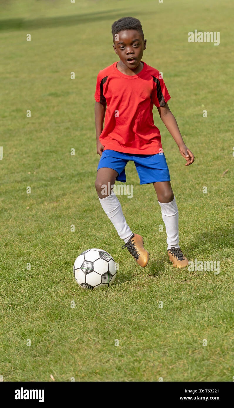 Hampshire, England, UK. April 2019. A nine year old footballer dribbles the soccer ball during a training session in a public park. - Stock Image