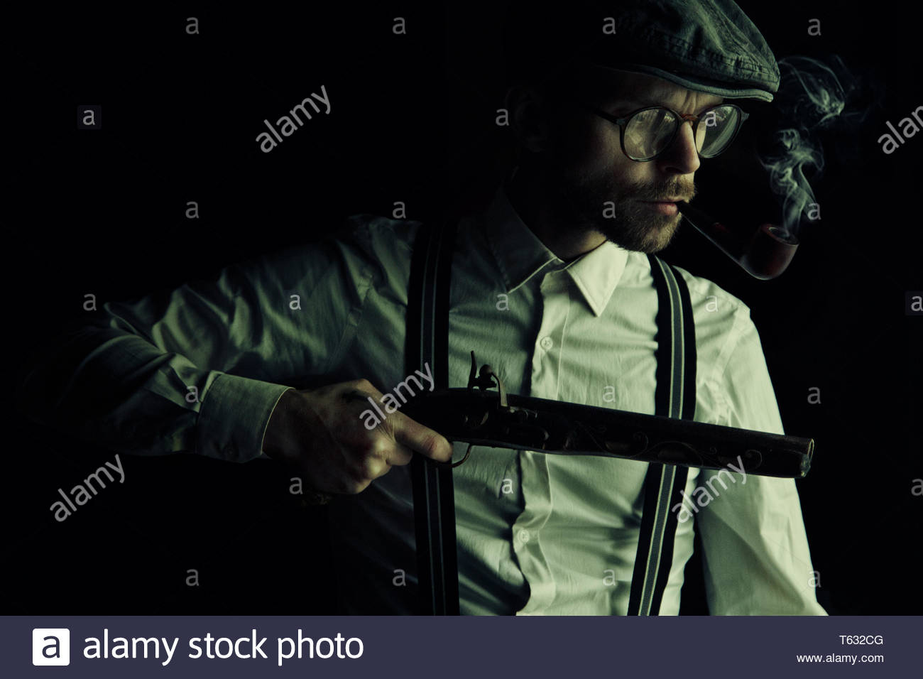 Old fashioned man with weapon in hand,  smoking pipe tobacco, wearing glasses, hat and braces - Stock Image