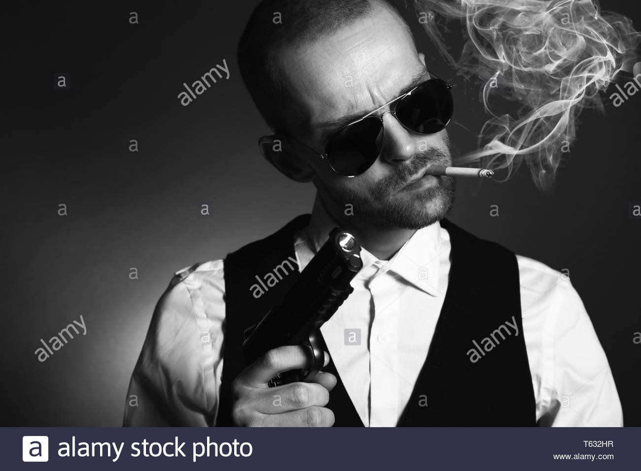 Dangerous gangster with gun and cigarette - Stock Image