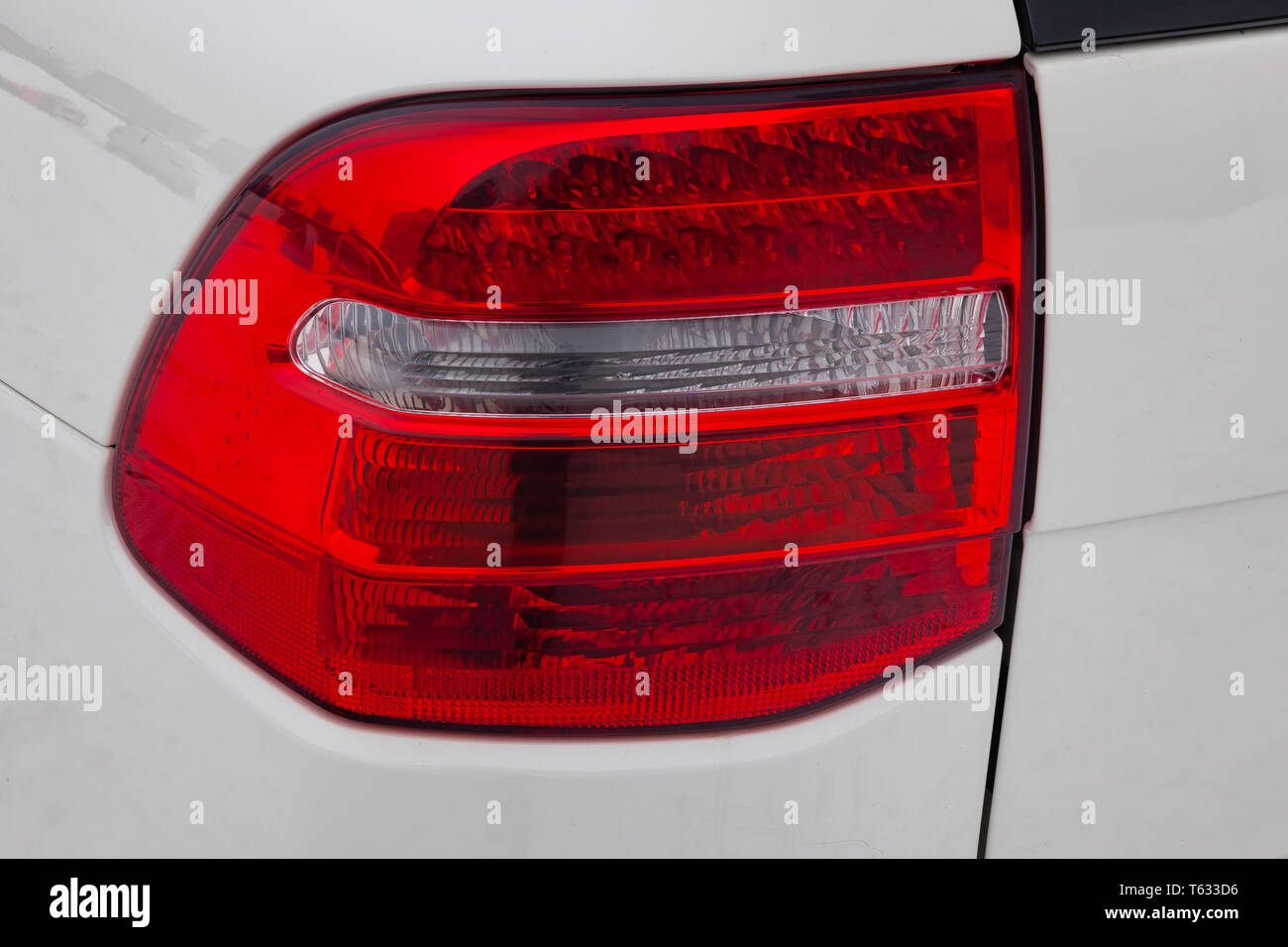 Close-up on the rear LED brake light of red color on a white car in the back of a suv after cleaning, polishing and detailing in the vehicle repair wo - Stock Image