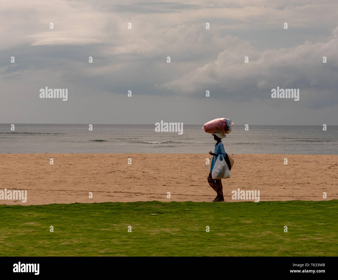 Bali, Indonesia -- February 29, 2016. An Indonesian woman carries goods in the traditional way as she walks on the beach. - Stock Image
