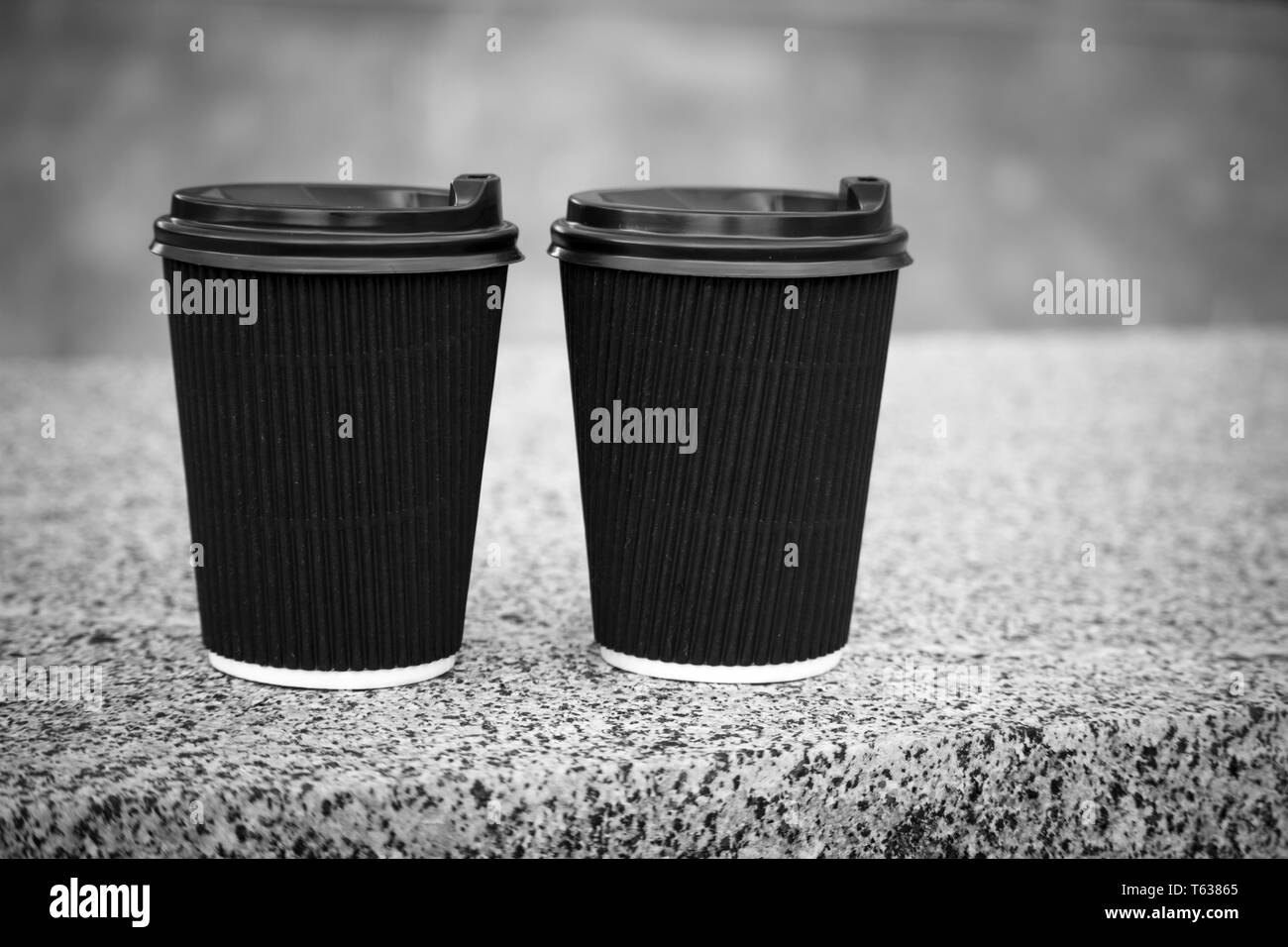 Two black disposable cups of coffee with lids are standing on the stone parapet, rest and a walk around the city, background or concept Stock Photo