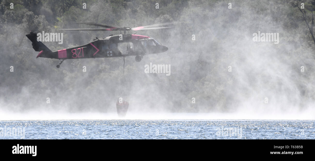 A U.S. Army UH-60 Black Hawk medium utility helicopter from the 1-140th Aviation Regiment dips its water bucket bucket in the Pardee Reservoir during annual joint aerial fire fighting training near Ione California, April 27, 2019. California Army and Air National Guard helicopters units train together alongside Cal Fire. The partnership enhances California aerial wild land fire fighting capabilities. (U.S. Air National Guard photo by Staff Sgt. Christian Jadot) - Stock Image