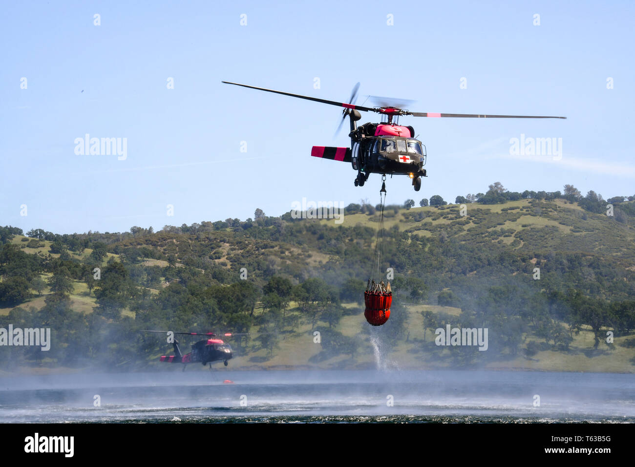 Two U.S. Army UH-60 Black Hawk medium utility helicopter from the 1-140th Aviation Regiment dips their water bucket bucket in the Pardee Reservoir during annual joint aerial fire fighting training near Ione California, April 27, 2019. California Army and Air National Guard helicopters units train together alongside Cal Fire. The partnership enhances California aerial wild land fire fighting capabilities. (U.S. Air National Guard photo by Staff Sgt. Christian Jadot) - Stock Image