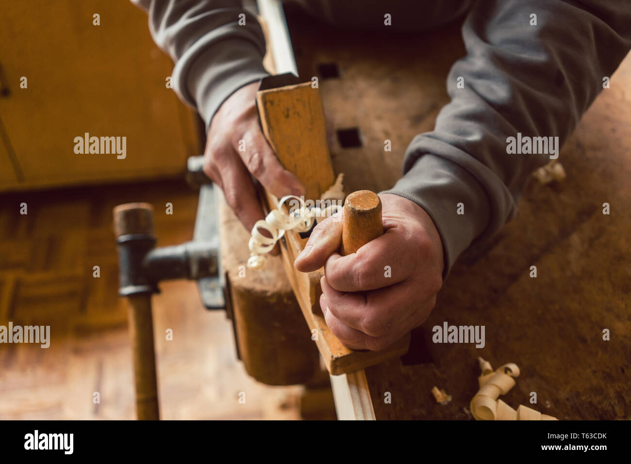 Top view of carpenter hand working with wood planer - Stock Image