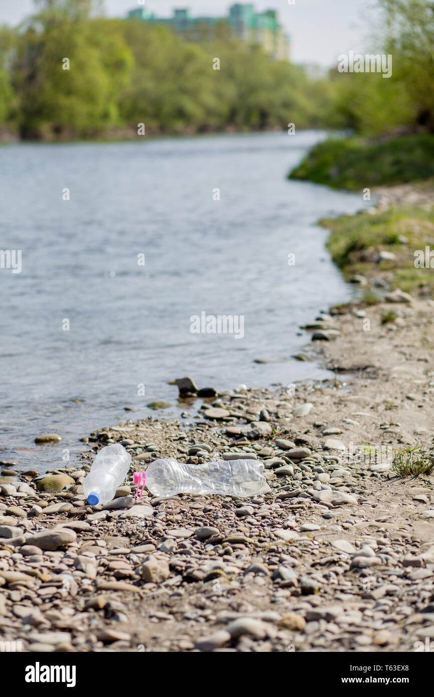River pollution near the shore, garbage near the river, plastic food waste, contributing to pollution. - Stock Image