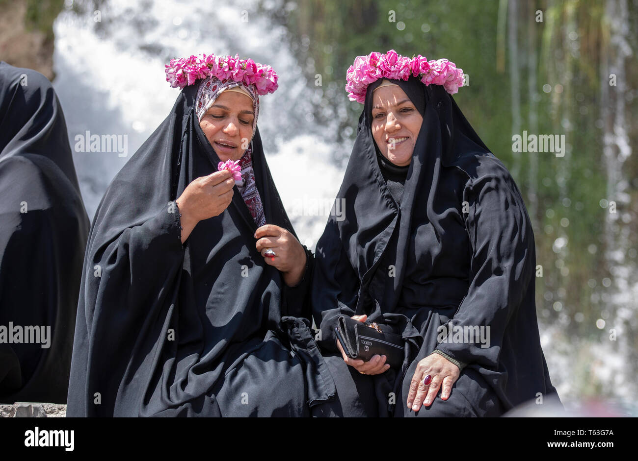 Kashan, Iran, 25th April 2019: iranian ladies with roses decorating their heads resting in front of a waterfall - Stock Image